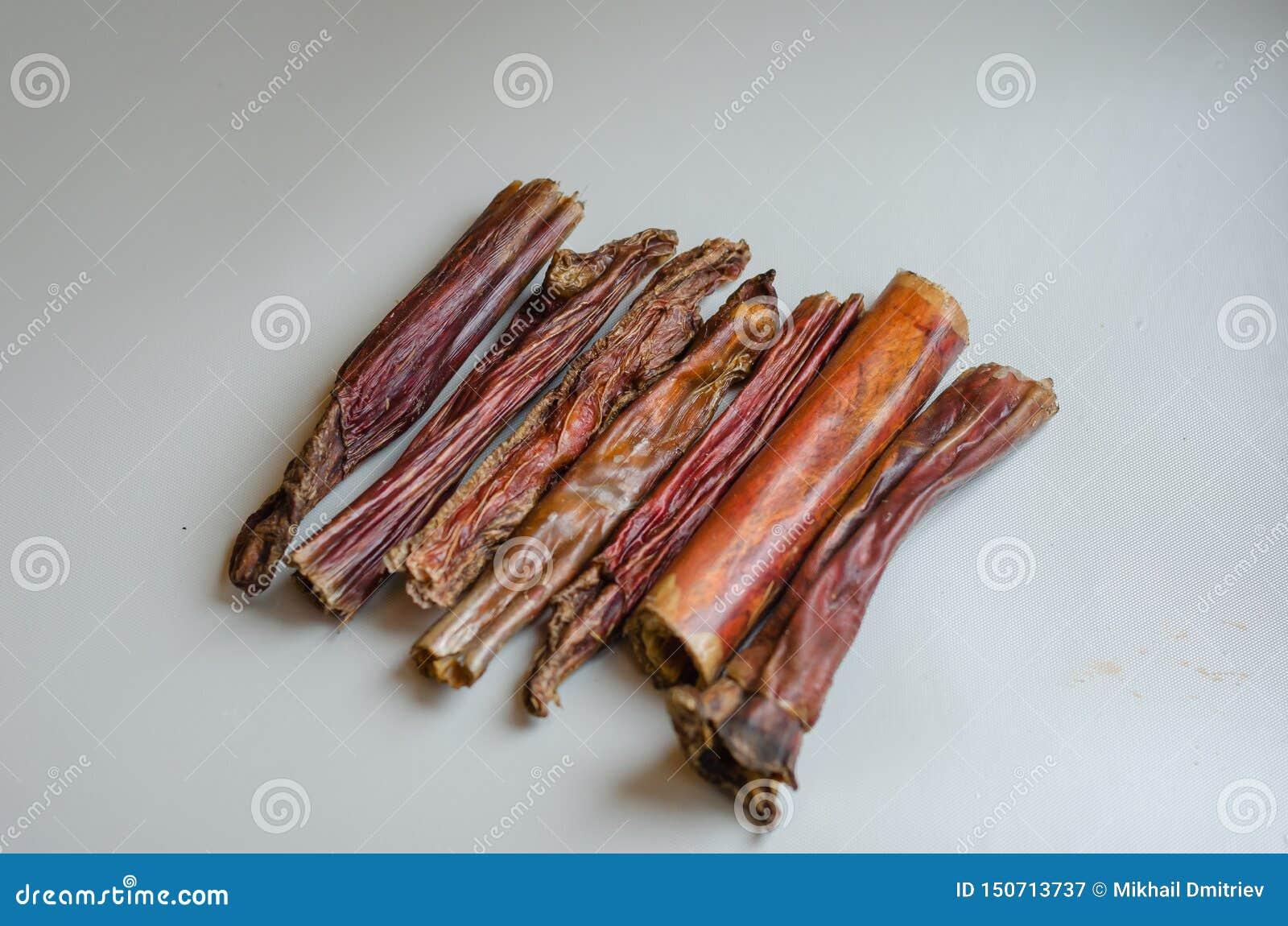 Μια μικρή χούφτα φοβερίζει τα ραβδιά σε ένα ελαφρύ υπόβαθρο Φυσικές απολαύσεις για τα σκυλιά Στεγνωμένος μασήστε Ξηρό βόειο κρέας