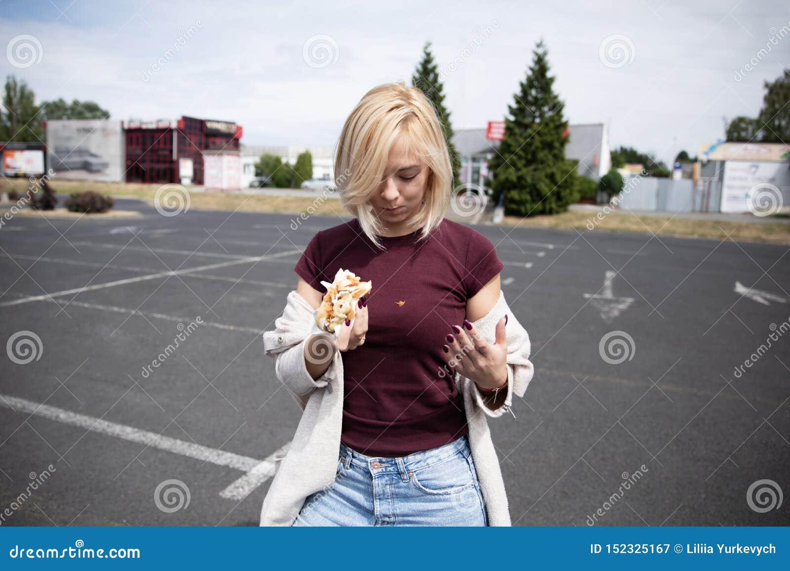 Μια νέα γυναίκα κρατά ένα δαγκωμένο χοτ-ντογκ