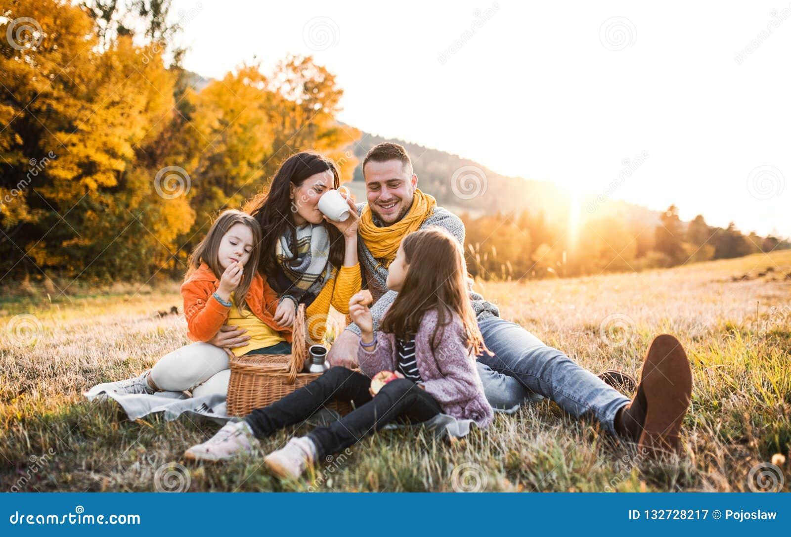 Μια νέα οικογένεια με δύο μικρά παιδιά που έχουν το πικ-νίκ στη φύση φθινοπώρου στο ηλιοβασίλεμα