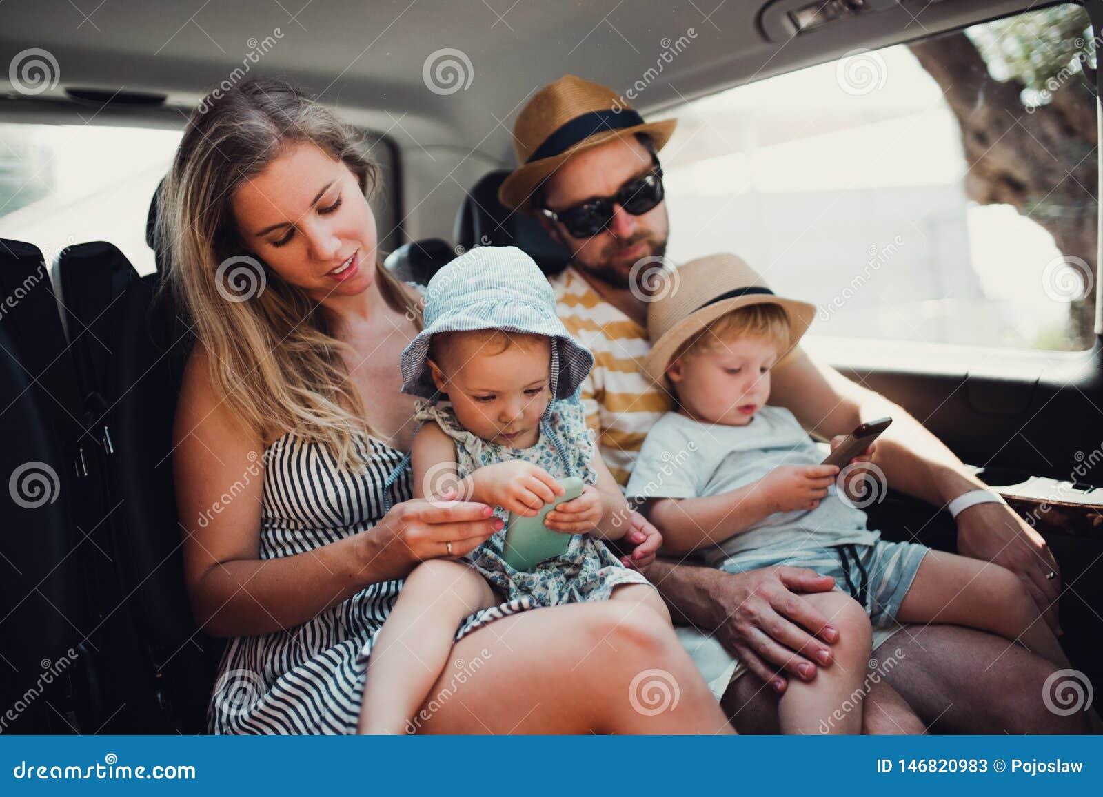 Μια νέα οικογένεια με δύο παιδιά μικρών παιδιών στο ταξί στις καλοκαιρινές διακοπές