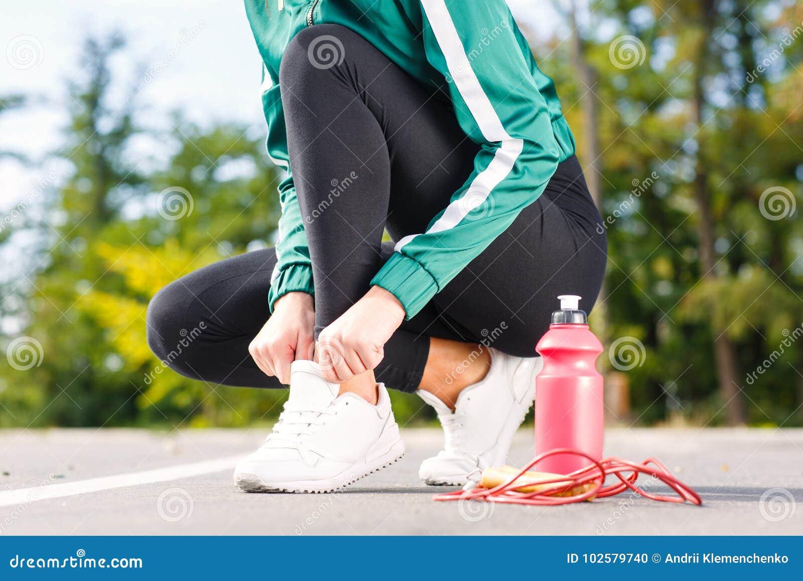 Μια νέα φίλαθλη γυναίκα εμπλέκει τα κορδόνια στα πάνινα παπούτσια Ένα κορίτσι με το τέλειο σώμα που κάνει τις ασκήσεις