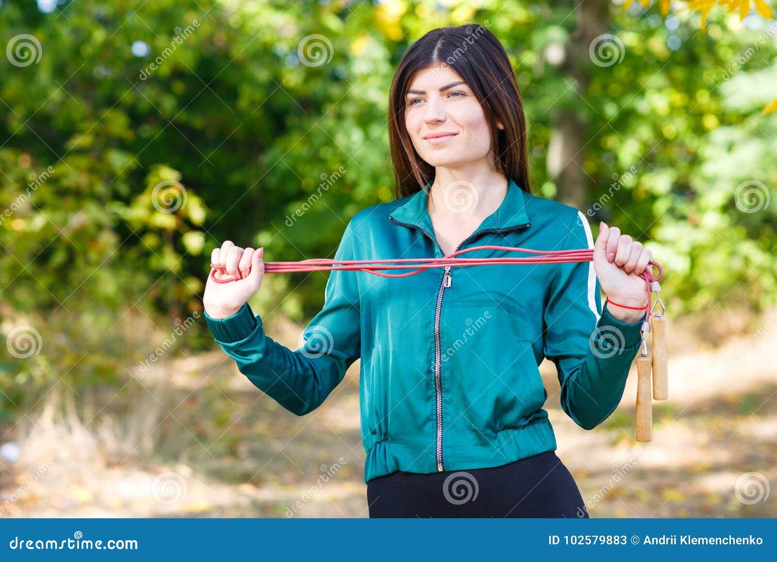 Μια νέα φίλαθλη γυναίκα με να κάνει σχοινιών πηδήματος ασκεί υπαίθριο