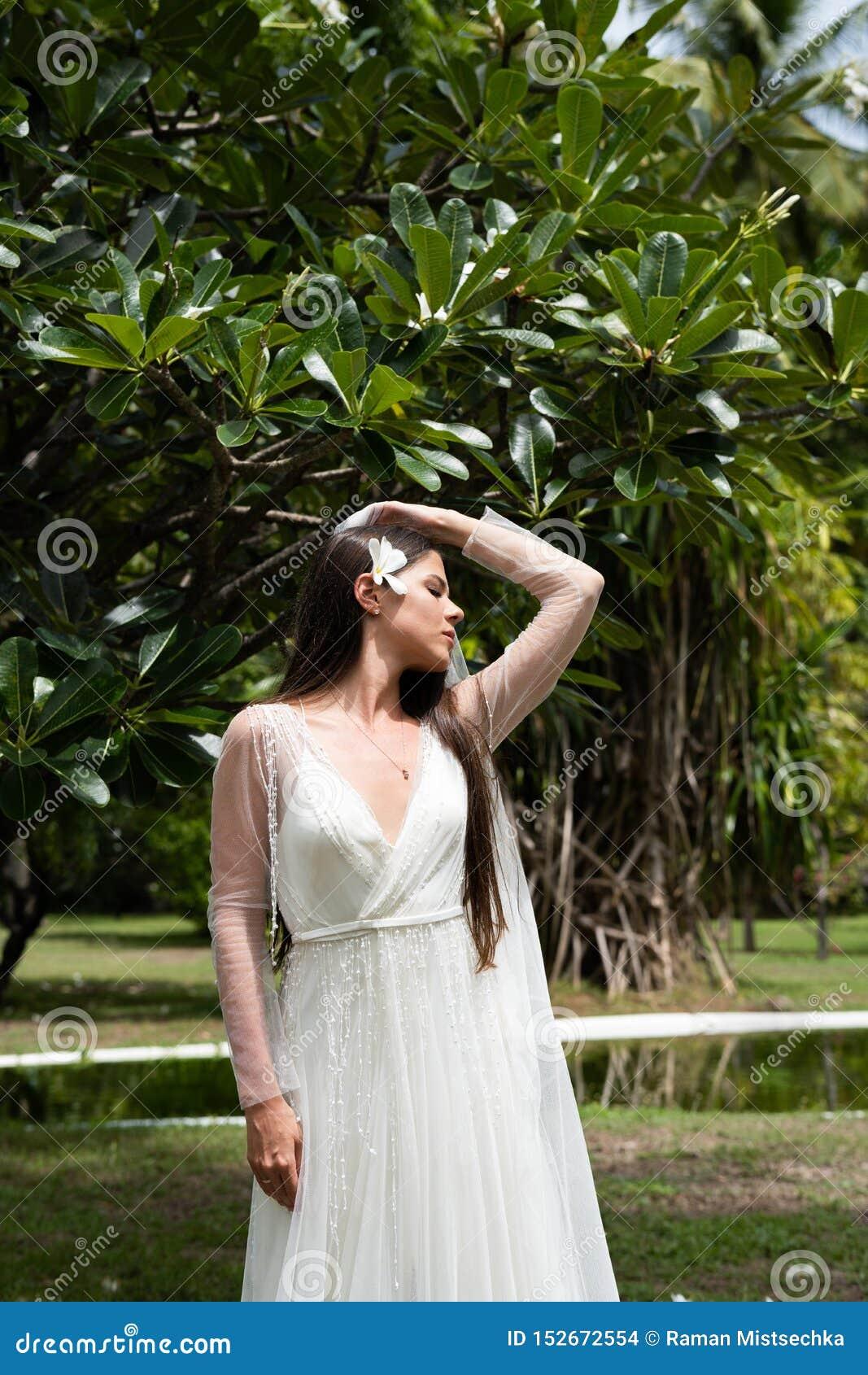 Μια νύφη σε ένα άσπρο φόρεμα με ένα εξωτικό λουλούδι στην τρίχα της στέκεται κάτω από ένα ανθίζοντας τροπικό δέντρο
