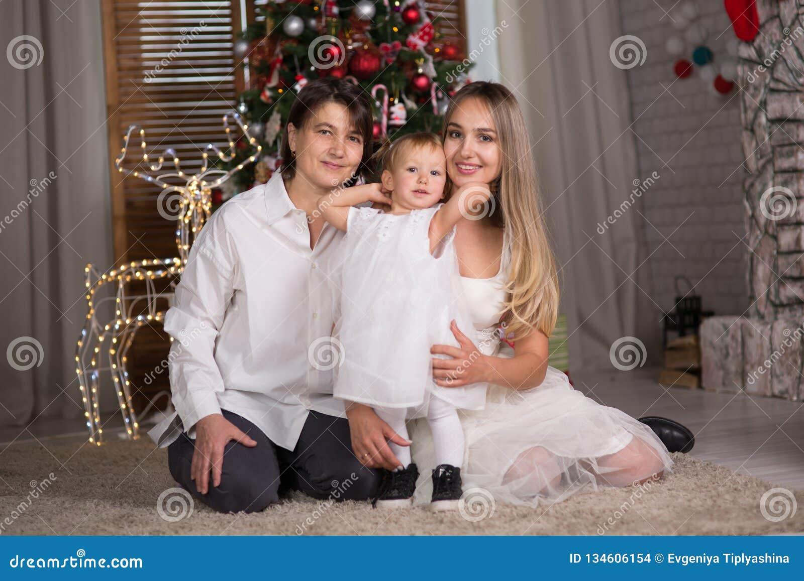 Μια οικογένεια με ένα μωρό κάθεται το κάθισμα κοντά στο χριστουγεννιάτικο δέντρο