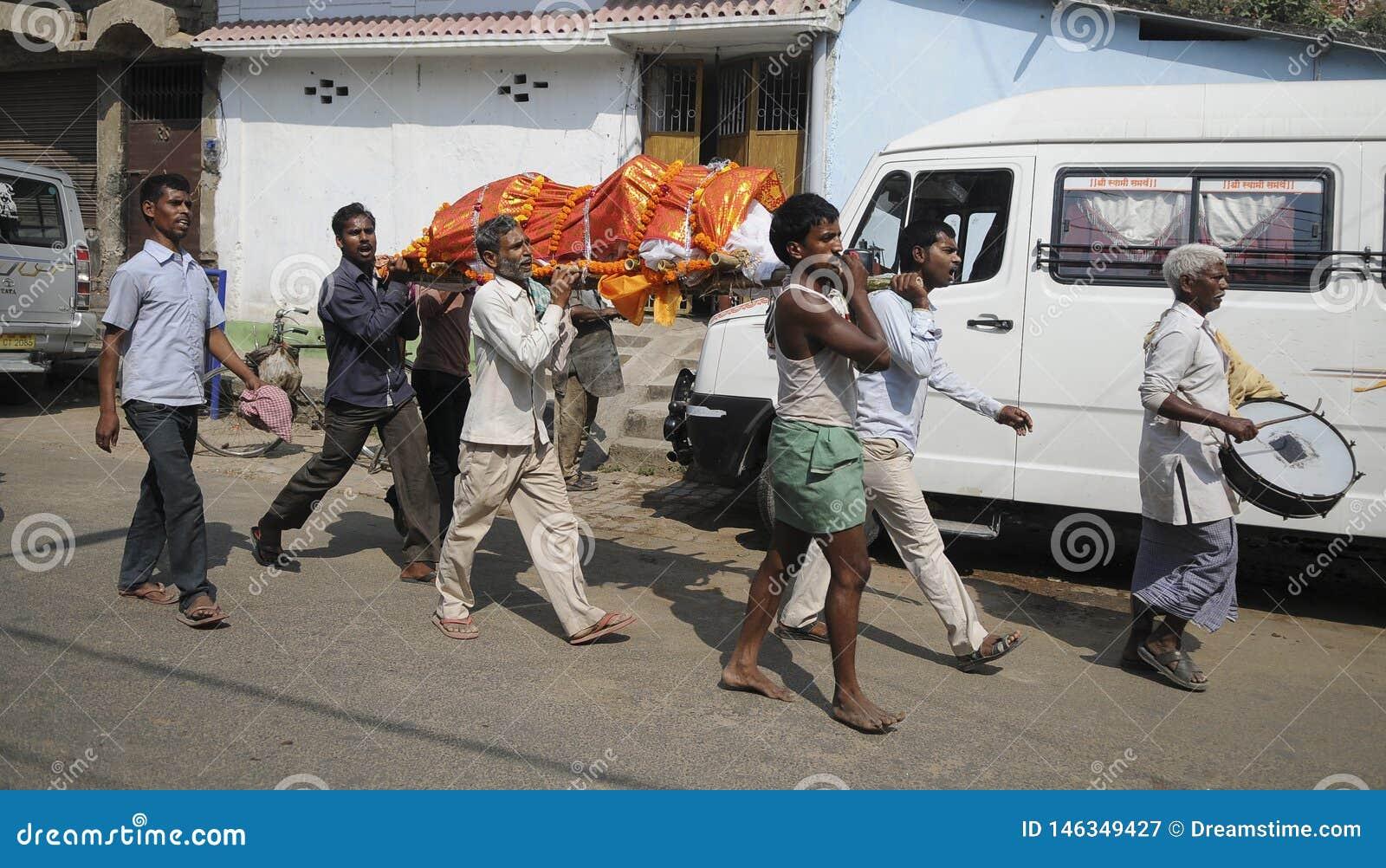 μια ομάδα ανθρώπων παίρνει ένα πτώμα στο Γάγκη που προετοιμάζεται για cremation