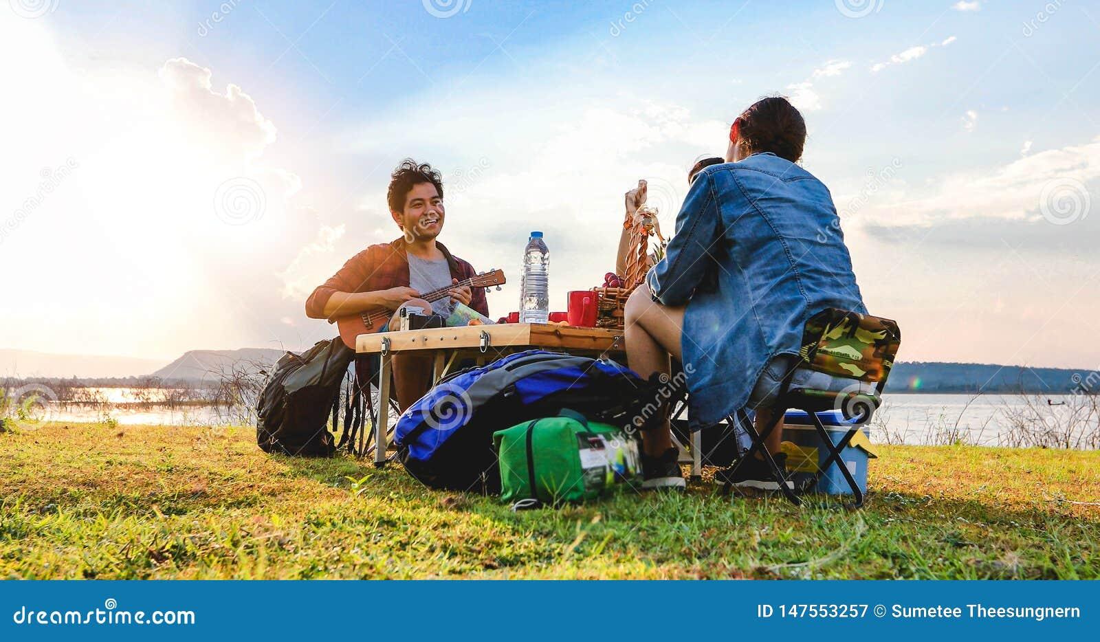 Μια ομάδα ασιατικών φίλων που παίζουν Ukelele και που ξοδεύουν το χρόνο που κάνει ένα πικ-νίκ στις καλοκαιρινές διακοπές Είναι ευ