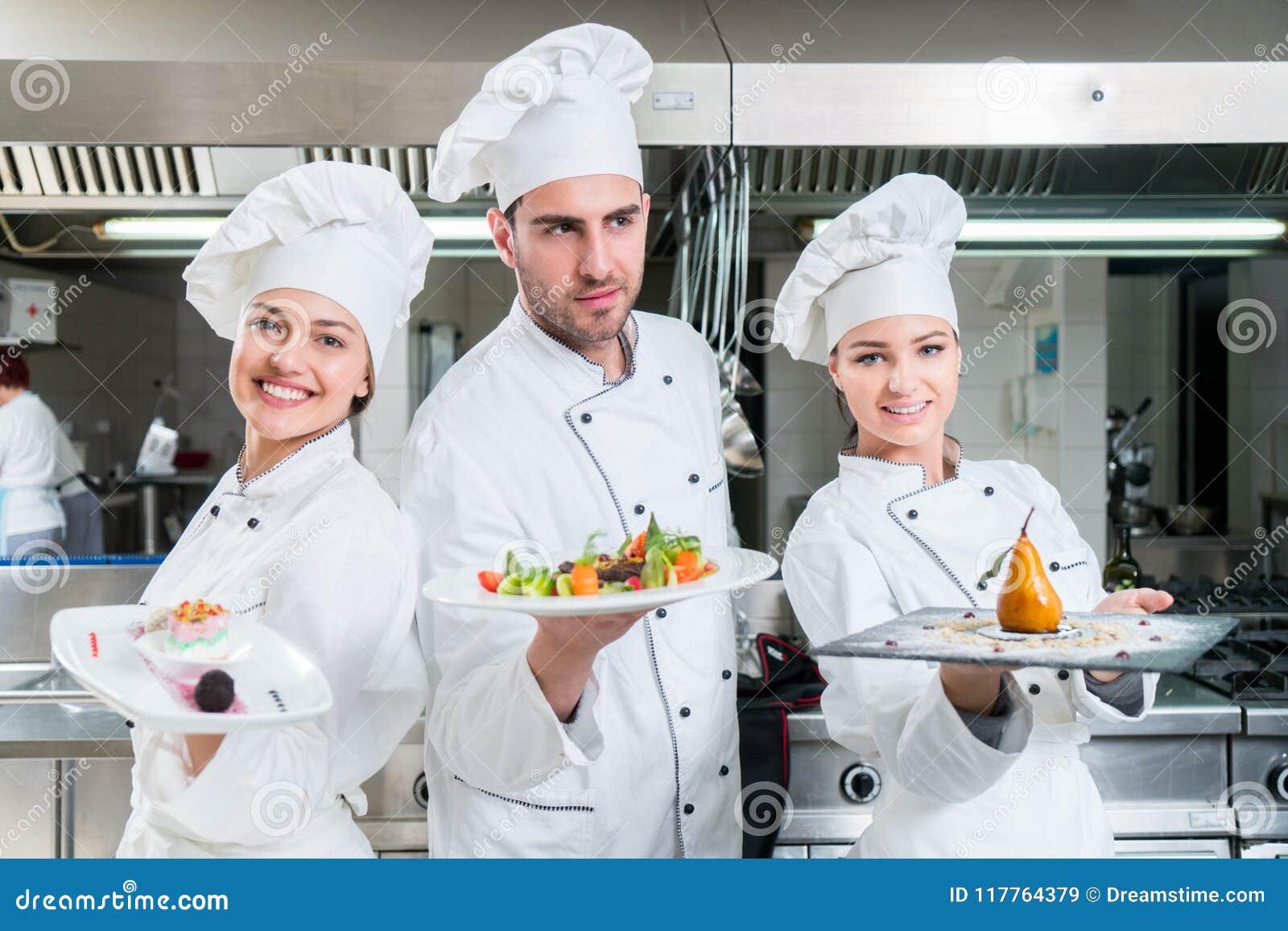 Μια ομάδα νέων αρχιμαγείρων posig με ένα γεύμα στο εστιατόριο πολυτέλειας