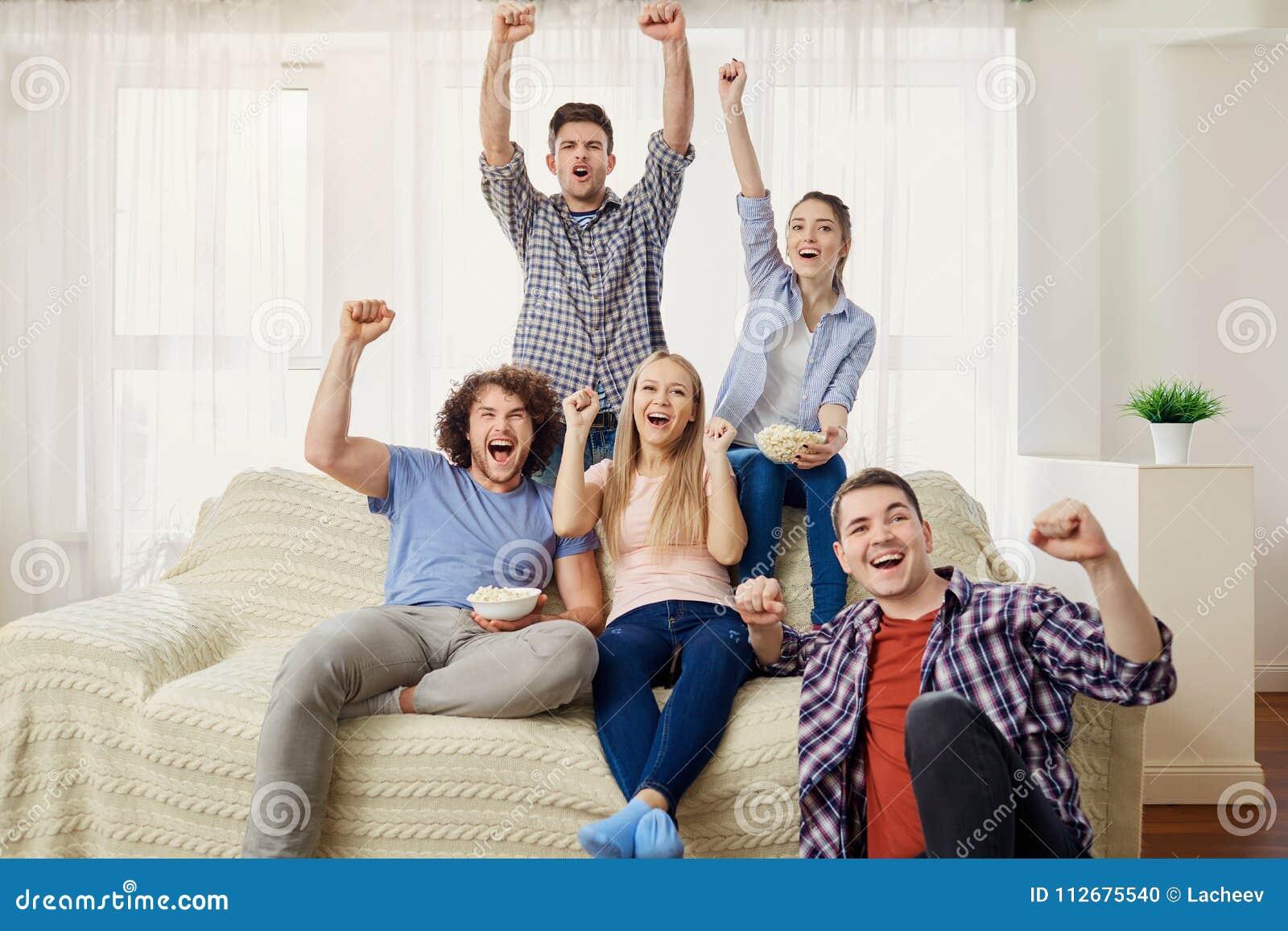 Μια ομάδα φίλων των ανεμιστήρων που προσέχουν μια συνεδρίαση αθλητικής TV σε ένα SOF
