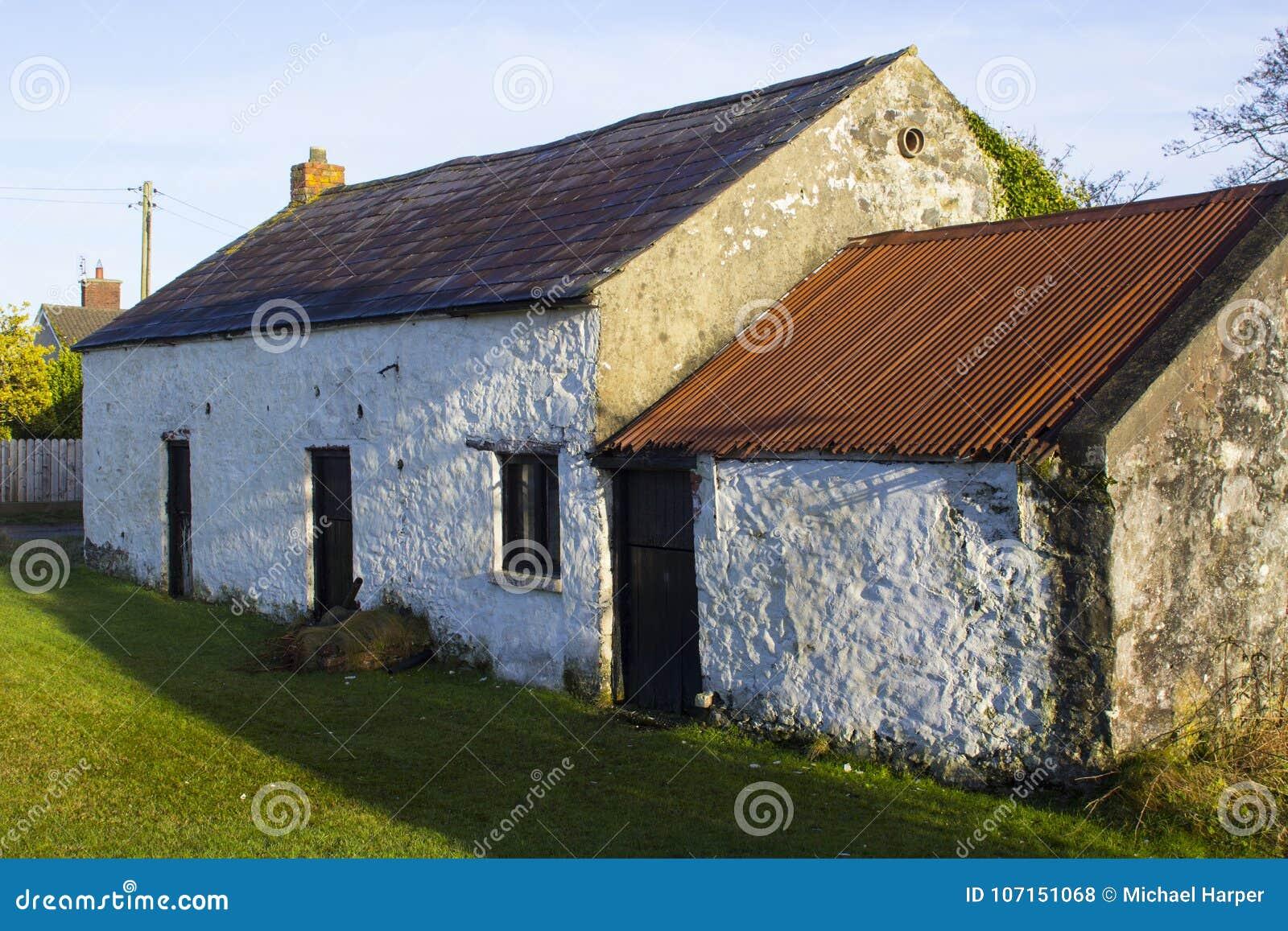 Μια παλαιά ασπρισμένη πέτρα έχτισε το ιρλανδικό εξοχικό σπίτι με ένα μικρό παράρτημα με τα μπλε κεραμίδια και τον οξυδώνοντας ζαρ