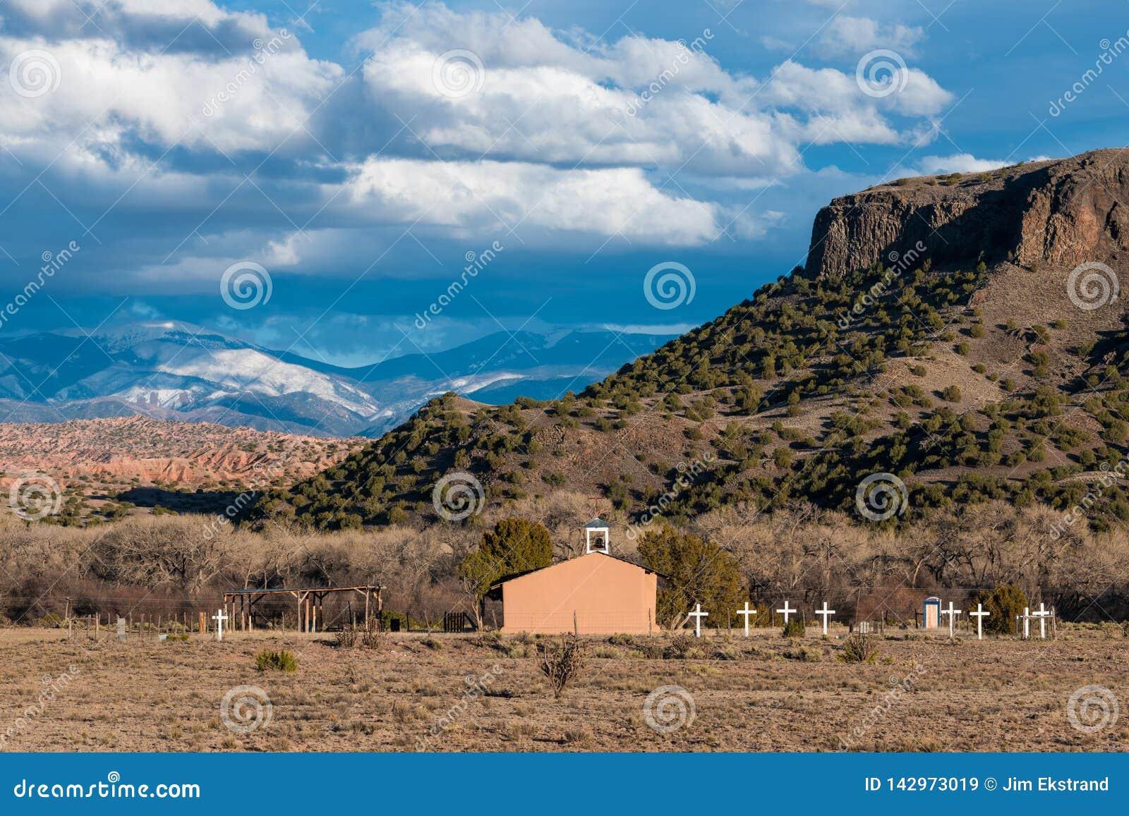 Μια παλαιά ισπανική εκκλησία ύφους αποστολής με μια σειρά των άσπρων σταυρών σε ένα νοτιοδυτικό τοπίο των mesas, badlands, και τω