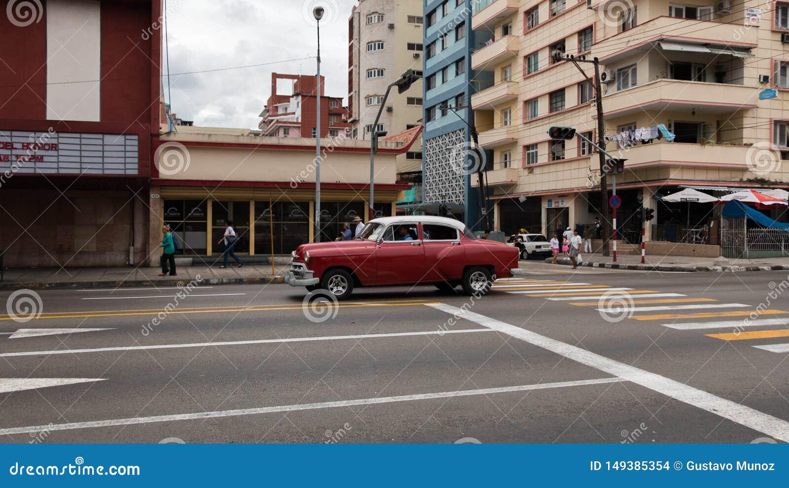 Μια παλαιά και όμορφη κόκκινη οδήγηση αυτοκινήτων μέσω των οδών της Αβάνας