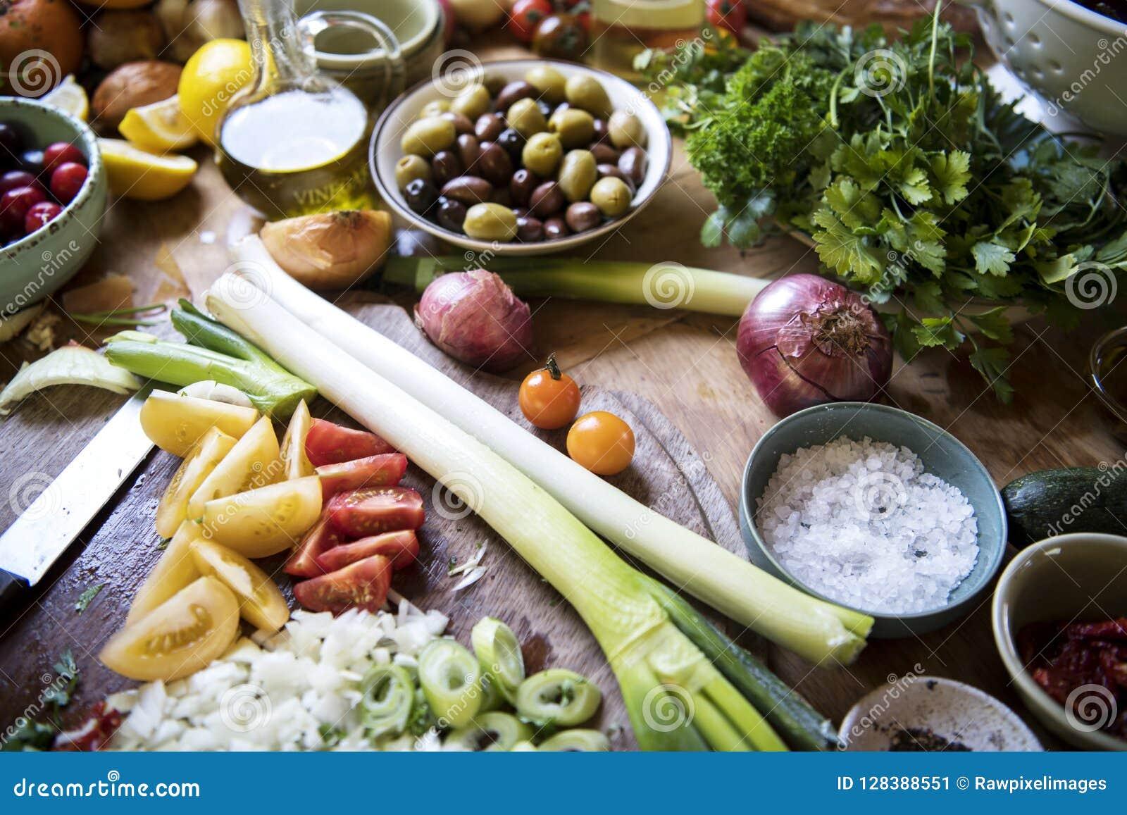 Μια πολυάσχολη κορυφή κουζινών με το λαχανικό και τα συστατικά