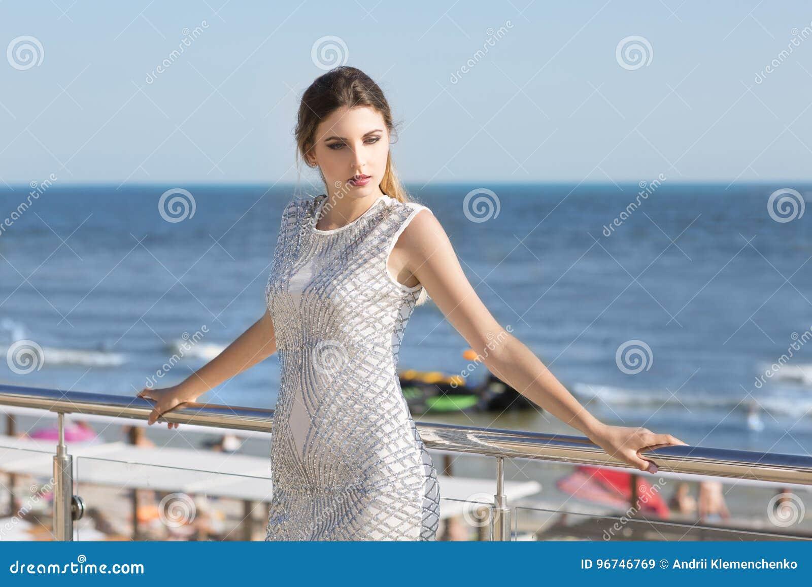 15176b757127 Μια θαυμάσια κυρία σε ένα χαλαρό και λαμπρό άσπρο φόρεμα σε ένα διαφανές  μπαλκόνι ξενοδοχείων ` s Η πανέμορφη γυναίκα με τη μαζευμένη σκοτεινή τρίχα  είναι ...