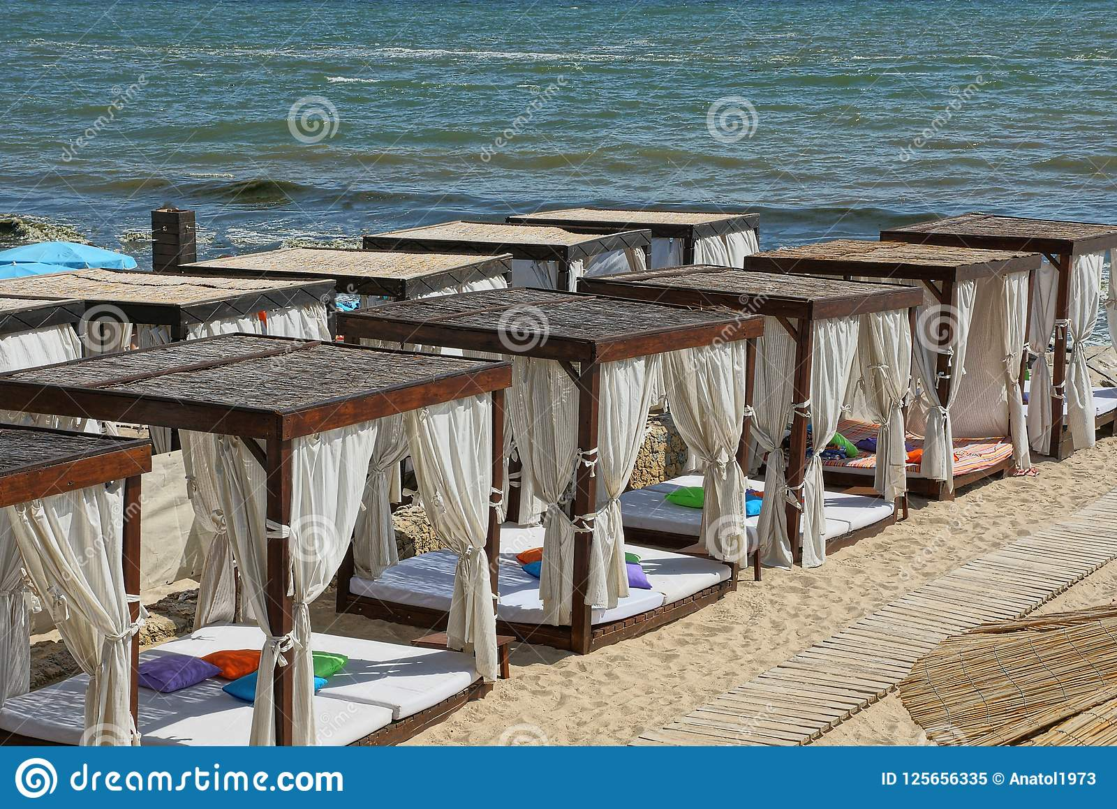 Μια σειρά των καφετιών ανοικτών περίπτερων με τις άσπρες κουρτίνες στην άμμο παραλιών κοντά στη θάλασσα