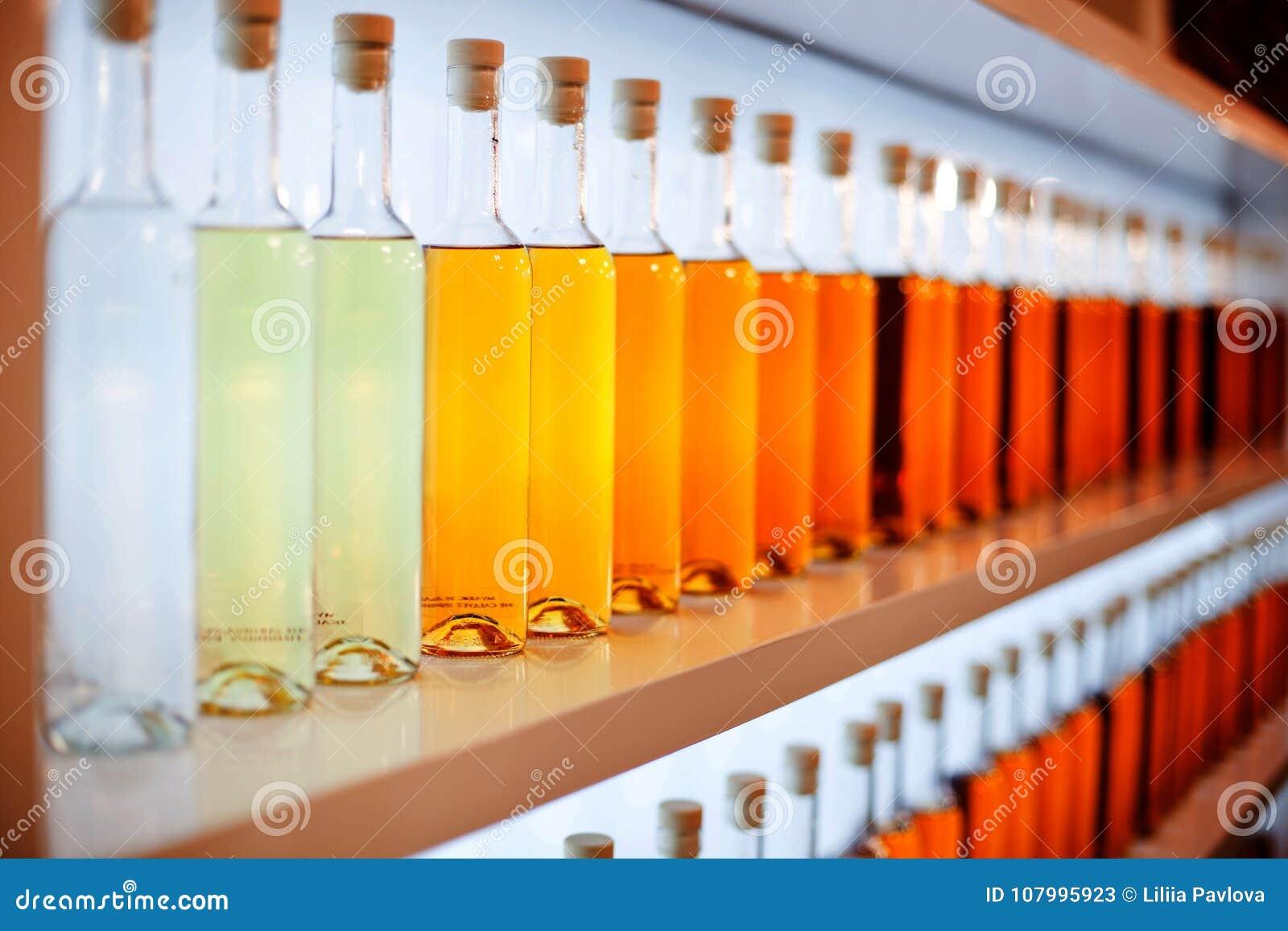 Μια σειρά των χρωματισμένων μπουκαλιών με το κονιάκ