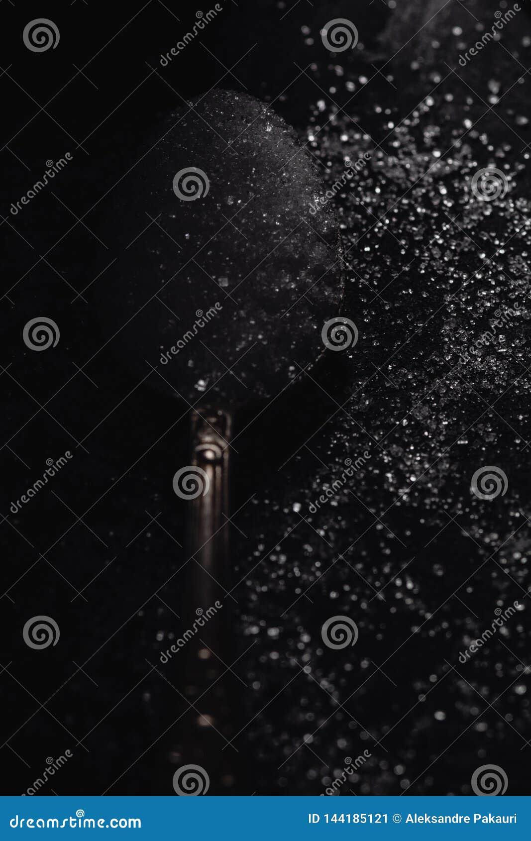 Μια σκοτεινή φωτογραφία ενός κουταλιού με την άσπρη ζάχαρη σε ένα μαύρο υπόβαθρο πετρών με τη διαστημική, τοπ άποψη αντιγράφων, σ