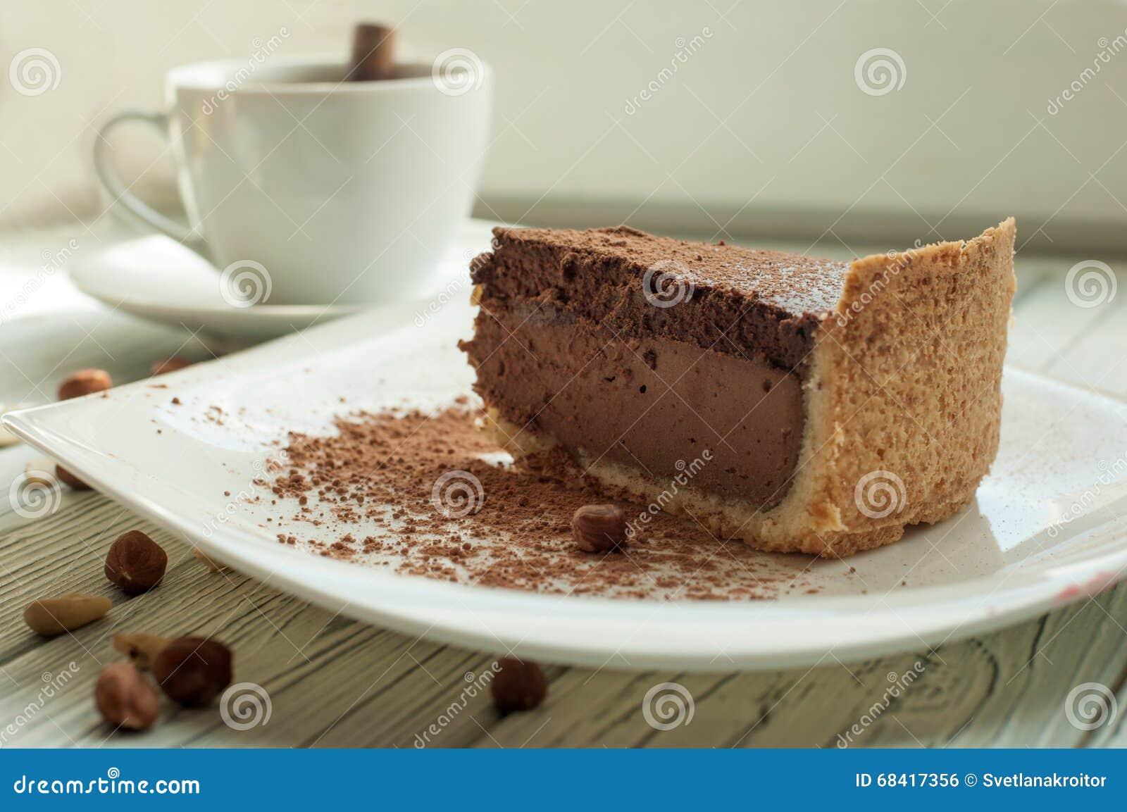 Μια σύνθεση με ένα φλυτζάνι του μαύρου καφέ και μια ειρήνη cheesecake σοκολάτας που διακοσμείται με τη σκόνη και τα καρύδια κακάο