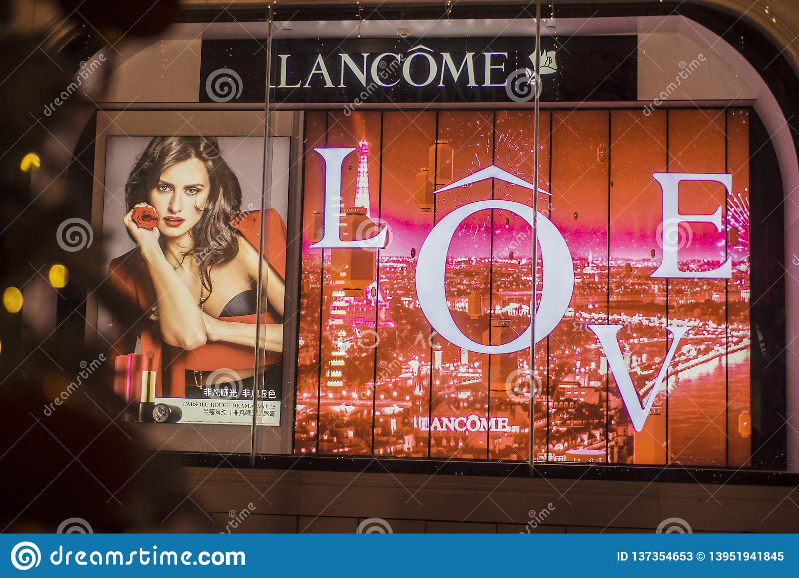 Μια τεράστια διαφήμιση για Lancome στο παράθυρο γυαλιού του καταστήματος νύχτας