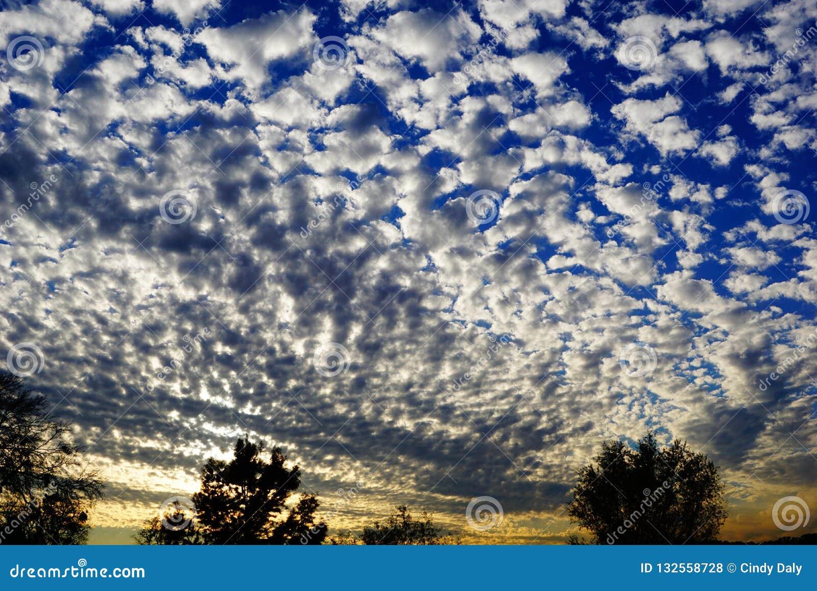 Μια φωτογραφία ενός ηλιοβασιλέματος με τα χνουδωτά σύννεφα