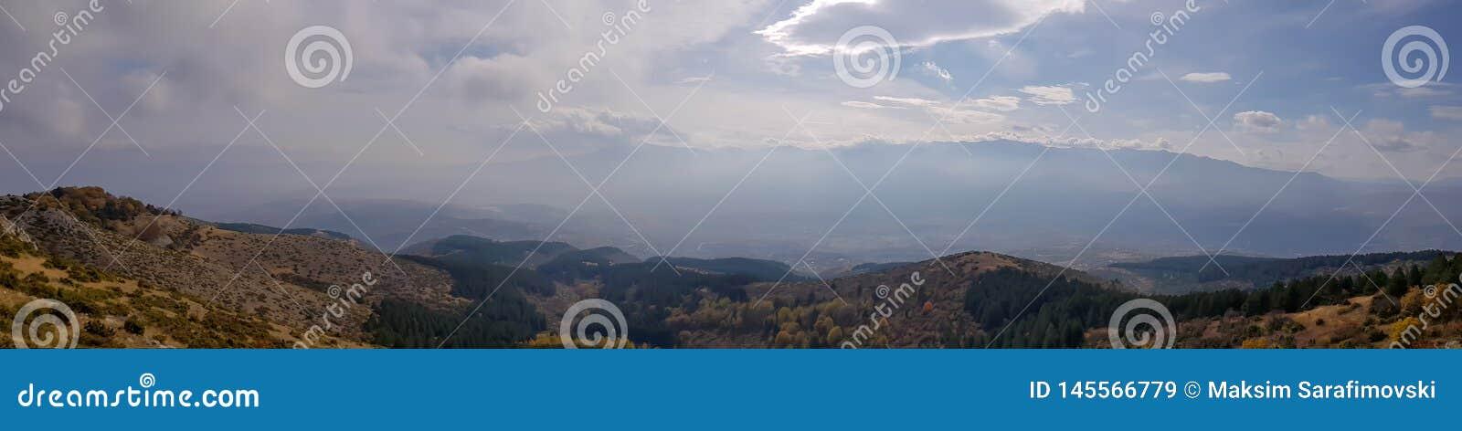 Μια φωτογραφία της σκιαγραφίας βουνών με την ομίχλη και την ηλιοφάνεια
