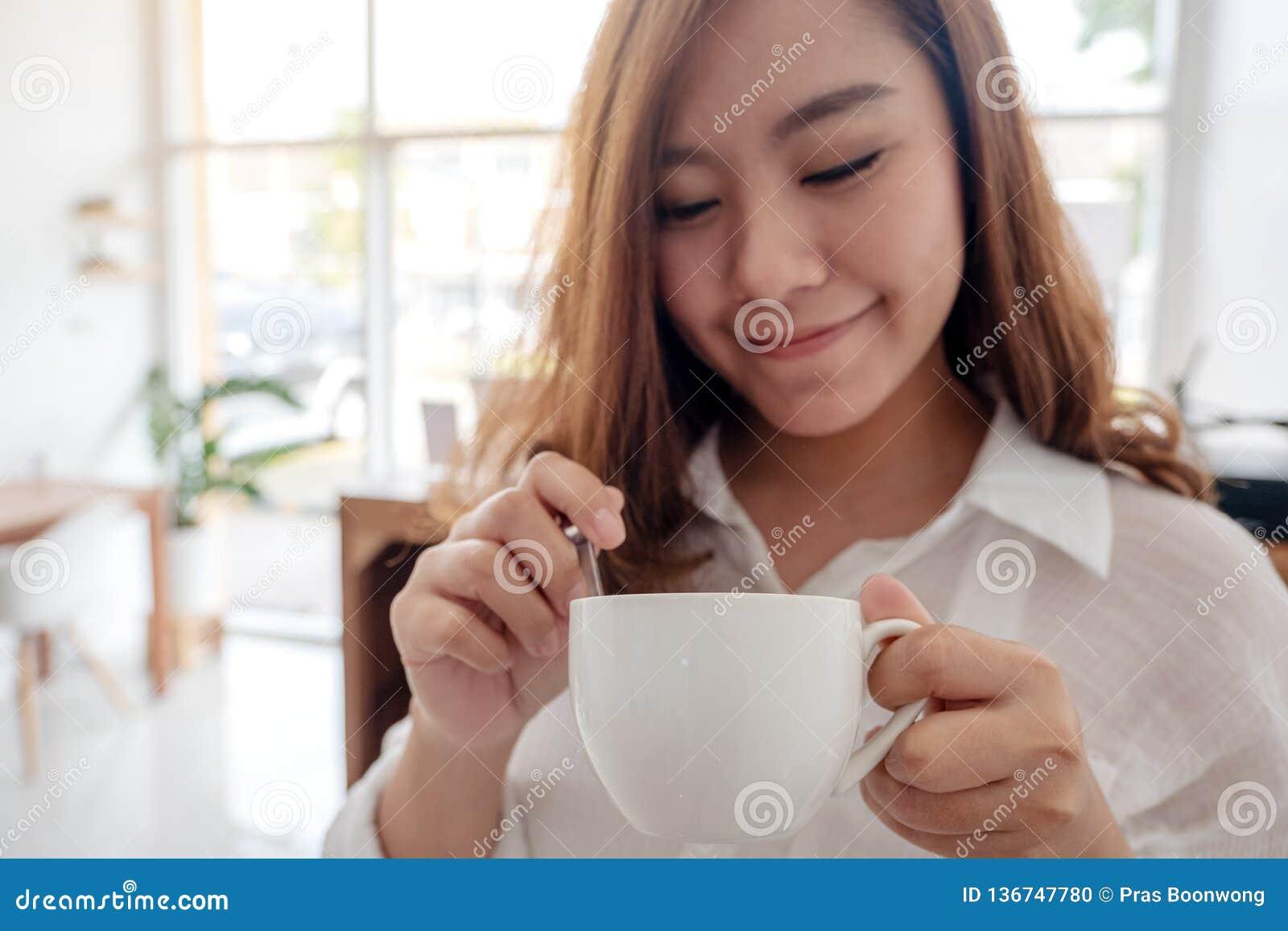 Μια όμορφη ασιατική γυναίκα που κρατά και που πίνει τον καυτό καφέ με το αίσθημα καλός στον εκλεκτής ποιότητας καφέ