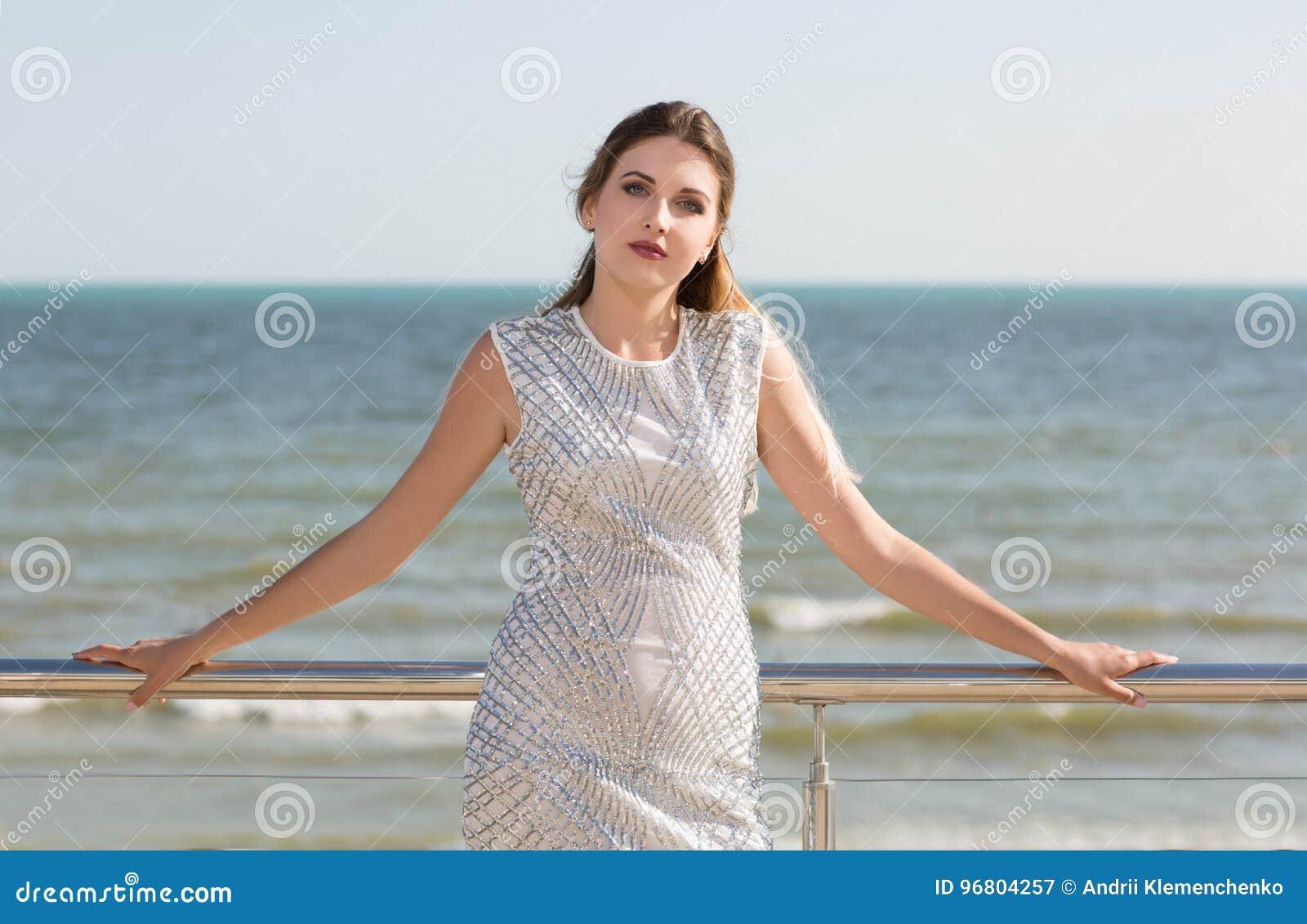 57fd1a04a853 Μια χαριτωμένη πρότυπη γυναίκα σε ένα φωτεινό μπλε συναρπαστικό υπόβαθρο  θάλασσας Γοητευτική κυρία σε ένα χαλαρό άσπρο φόρεμα με τα μπλε σχέδια  κοντά στη ...