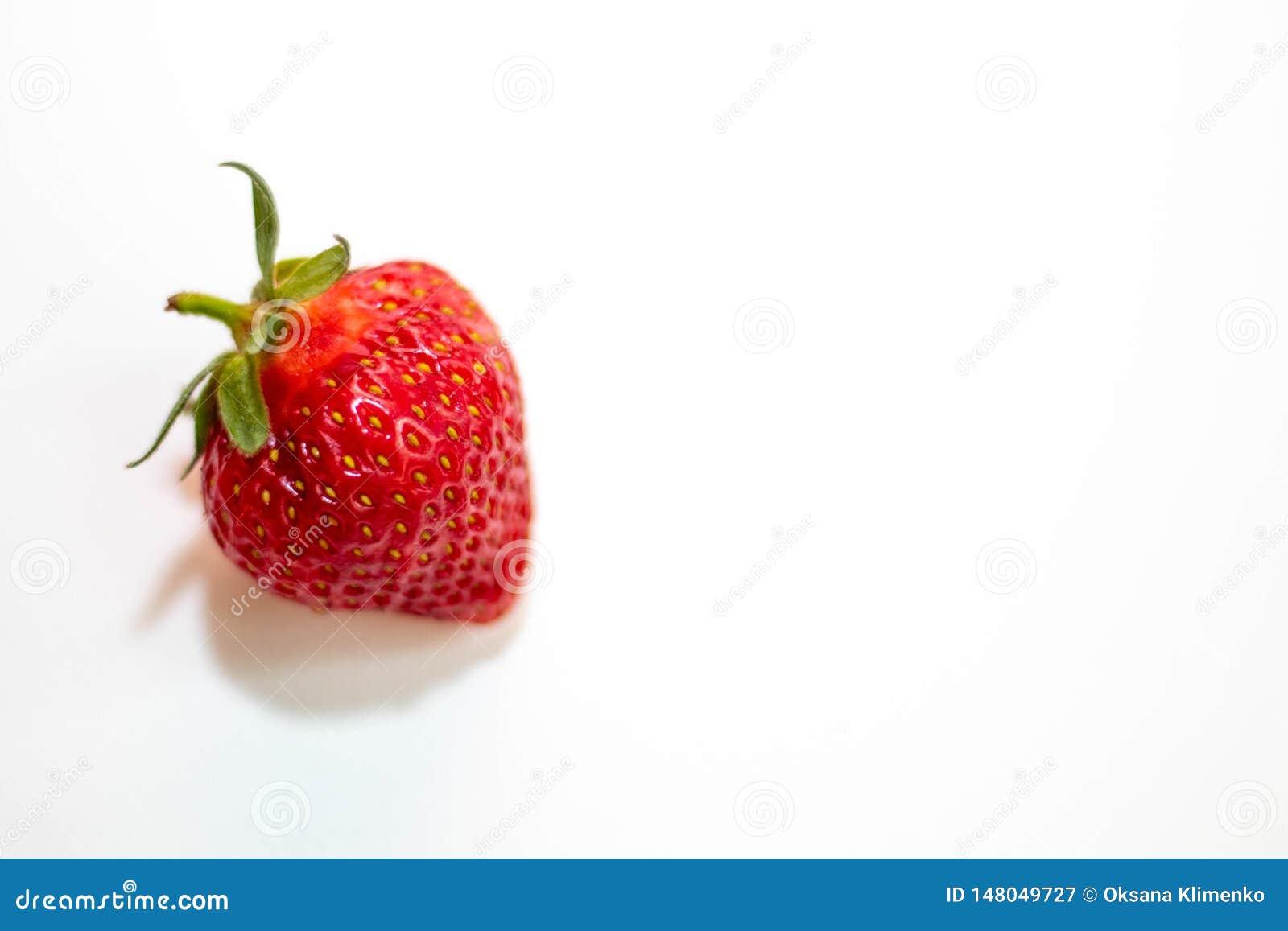 Μια όμορφη κόκκινη φράουλα με μια πράσινη ουρά βρίσκεται σε ένα άσπρο υπόβαθρο