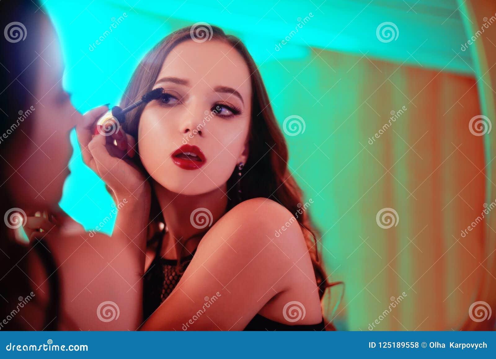 Μια όμορφη νέα γυναίκα γίνεται ένα makeover Κορίτσι με cerly την τρίχα που κάνει το βράδυ makeup που χρησιμοποιεί Mascara