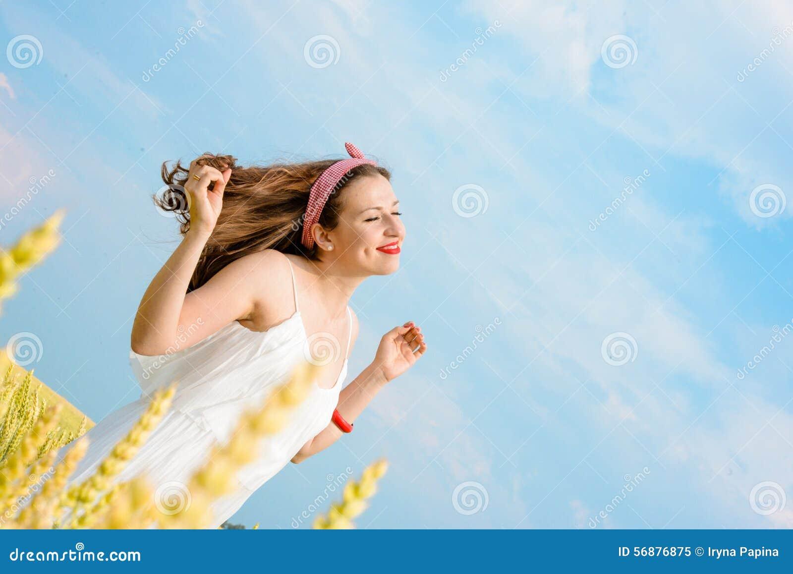 Μια όμορφη νέα γυναίκα σε έναν τομέα σίτου