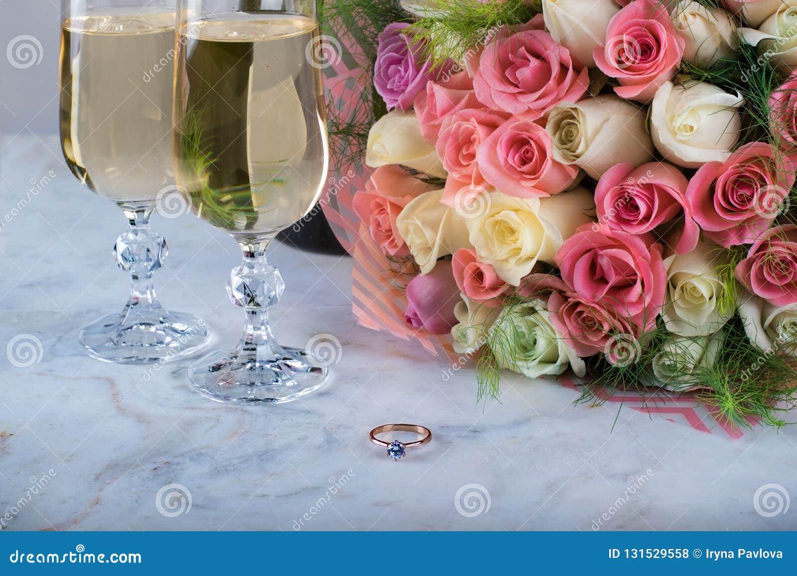 Μια όμορφη νυφική ανθοδέσμη των λεπτών τριαντάφυλλων, ένα δαχτυλίδι με ένα διαμάντι, δύο ποτήρια της σαμπάνιας σε έναν μαρμάρινο