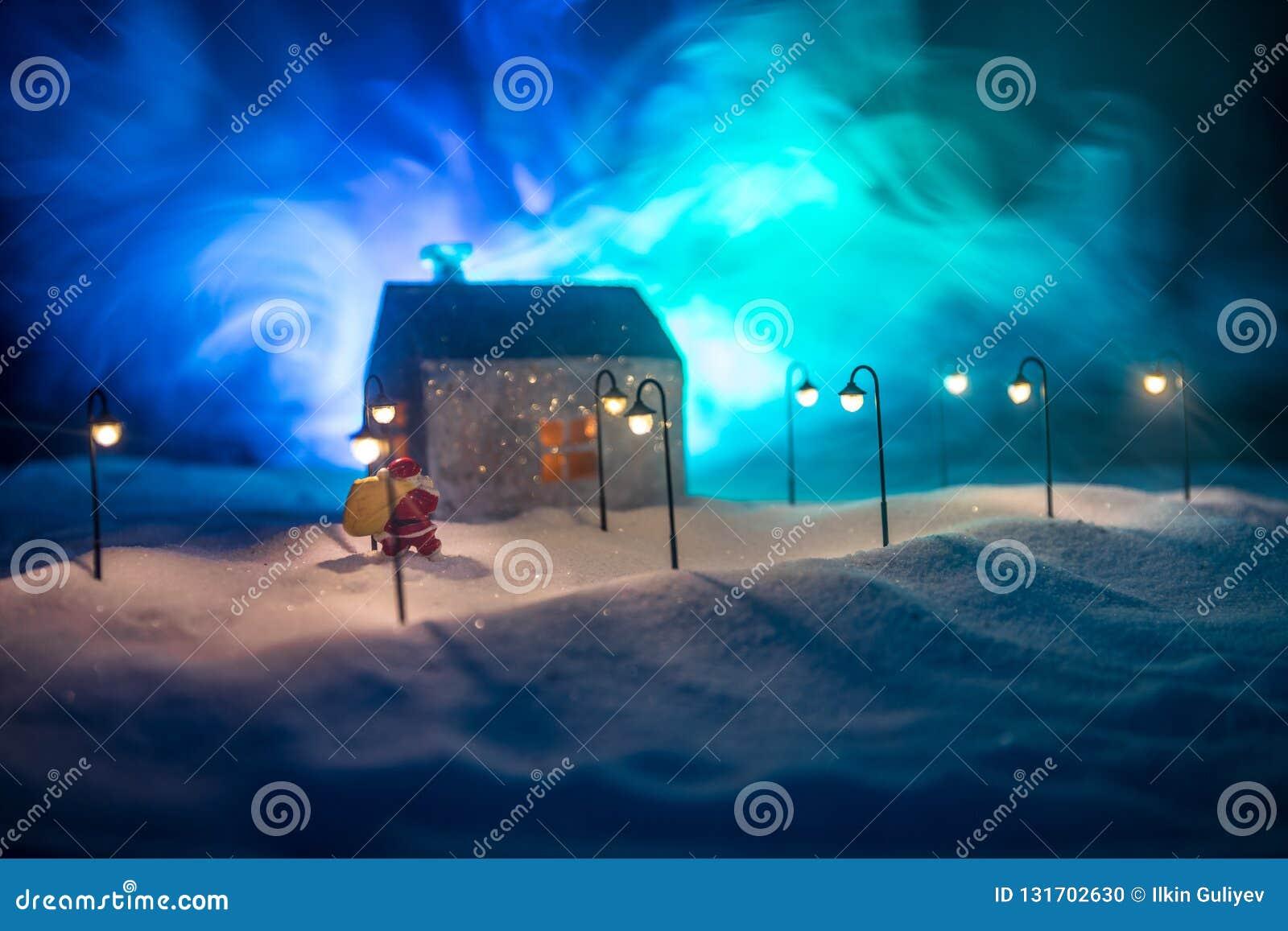 Μικρά διακοσμητικά χαριτωμένα μικρά σπίτια στο χιόνι τη νύχτα το χειμώνα, τα Χριστούγεννα και το νέο μικροσκοπικό σπίτι έτους στο