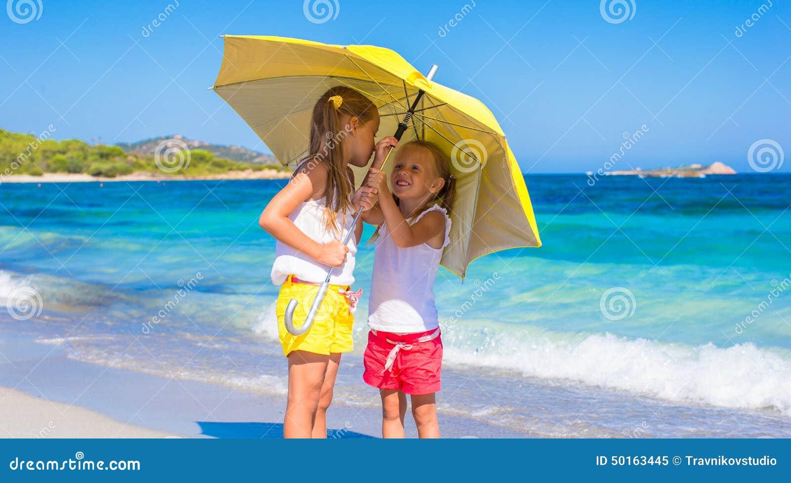 Μικρά κορίτσια με τη μεγάλη κίτρινη ομπρέλα κατά τη διάρκεια
