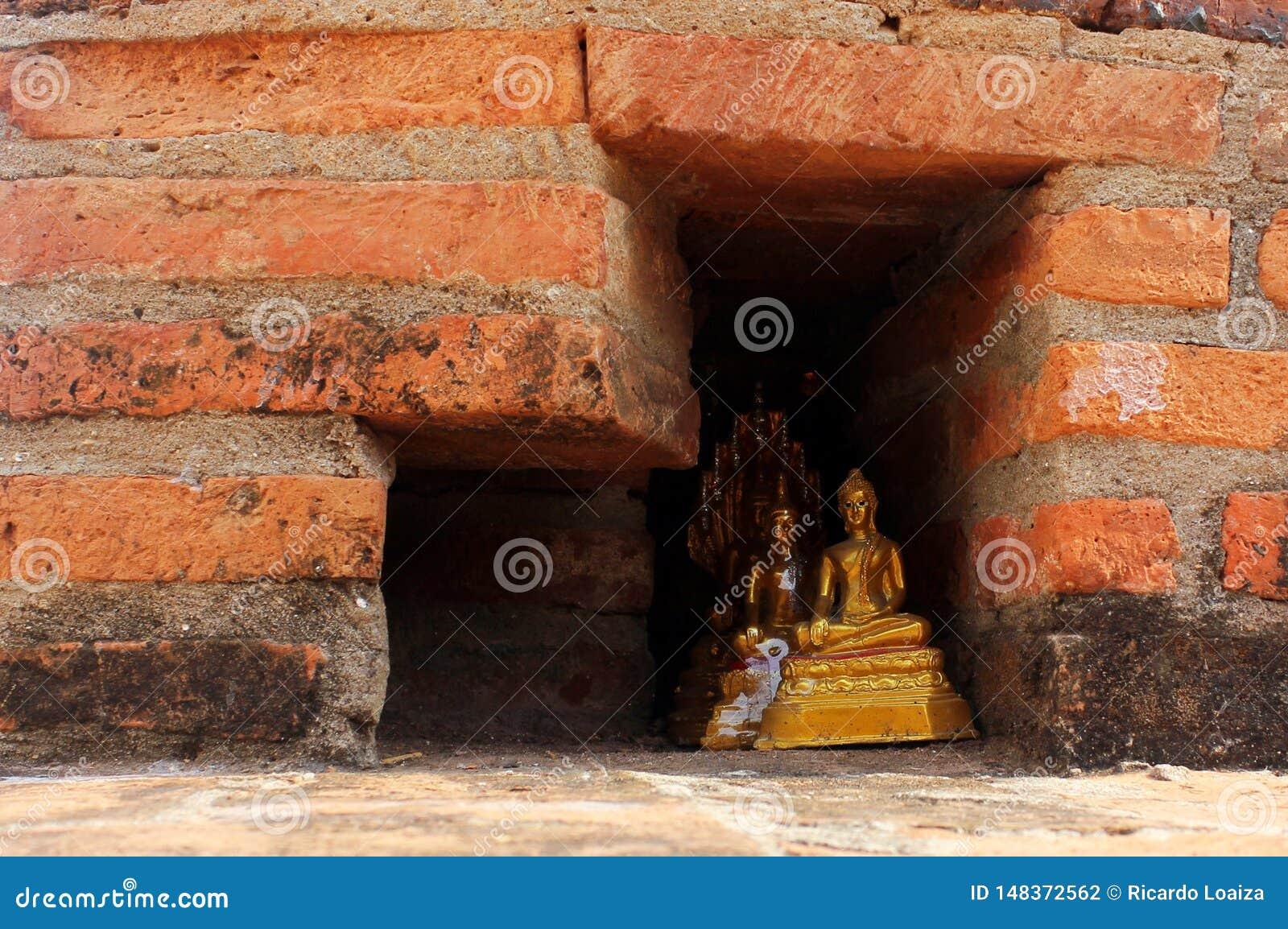 Μικρά χρυσά αγάλματα του Βούδα που κρύβονται σε έναν τούβλινο τοίχο