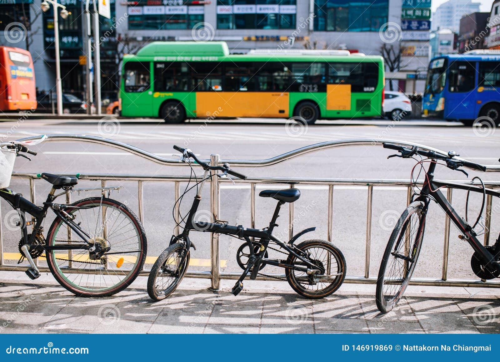 Μικροσκοπικό διπλώνοντας ποδήλατο στην οδό πόλεων πάρκο στο φράκτη sideroad, την αστική σκηνή, το ποδήλατο και το λεωφορείο