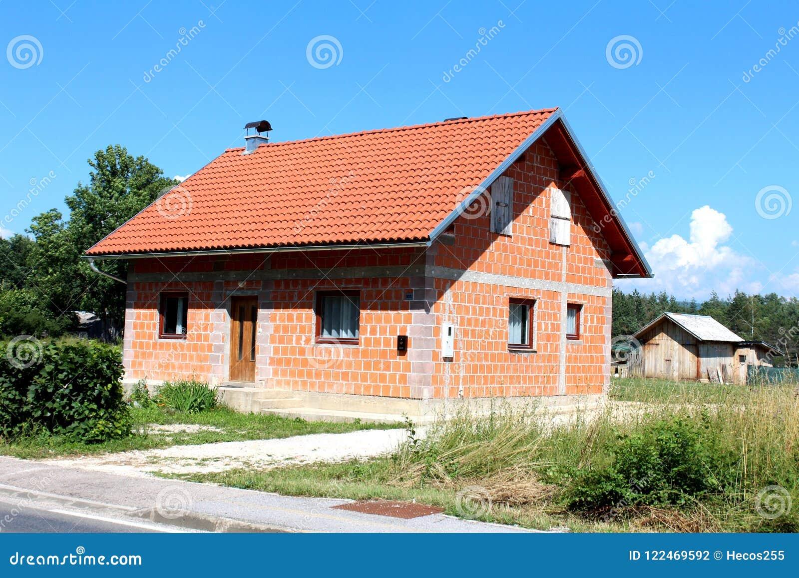 Μικρό ατελές προαστιακό οικογενειακό σπίτι τούβλου με το παλαιό ξύλινο υπόστεγο στο υπόβαθρο