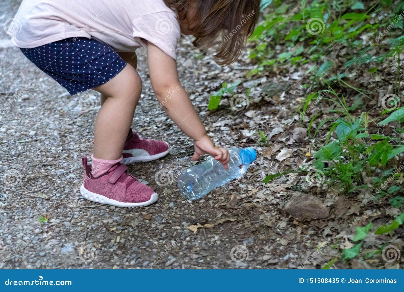 Μικρό κορίτσι, έγκυες μητέρα και γιαγιά που καθαρίζουν το δάσος των πλαστικών