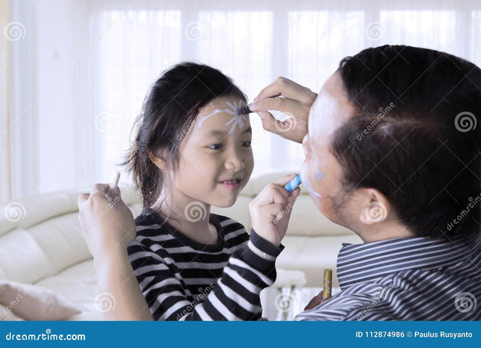 Μικρό κορίτσι και ο πατέρας της που κάνουν τη ζωγραφική προσώπου