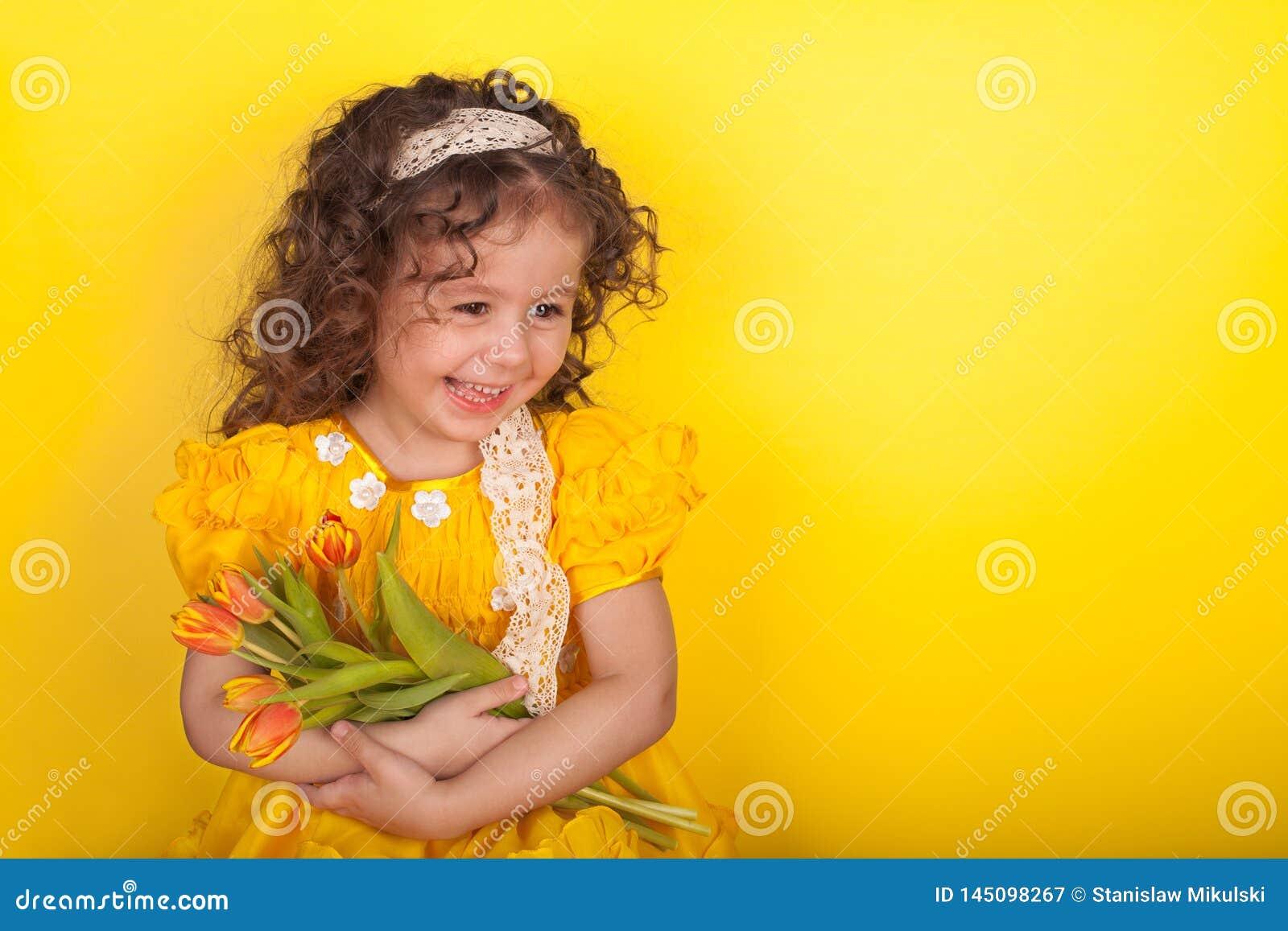 Μικρό κορίτσι με τις τουλίπες στα χέρια στο κίτρινο υπόβαθρο