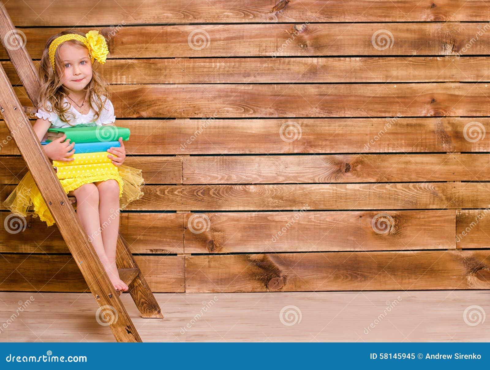 Μικρό κορίτσι με το σωρό των βιβλίων που κάθεται στη σκάλα