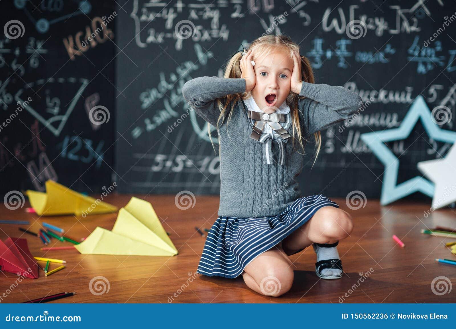 Μικρό κορίτσι ξανθό στα χέρια εκμετάλλευσης σχολικών στολών στο κεφάλι της , ανοίξτε το στόμα του ενάντια στον πίνακα κιμωλίας με