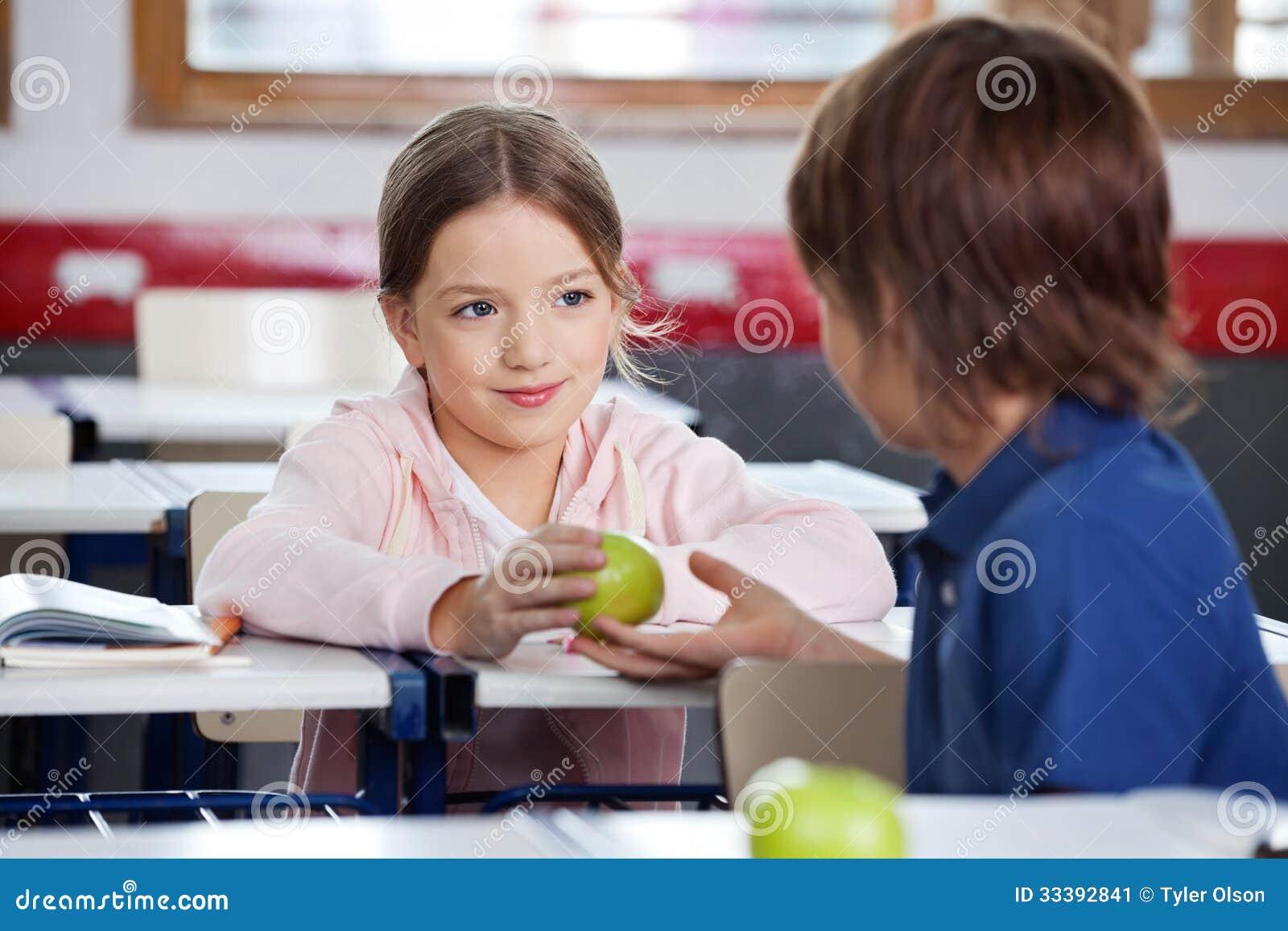 Μικρό κορίτσι που δίνει τη Apple στο αγόρι στην τάξη