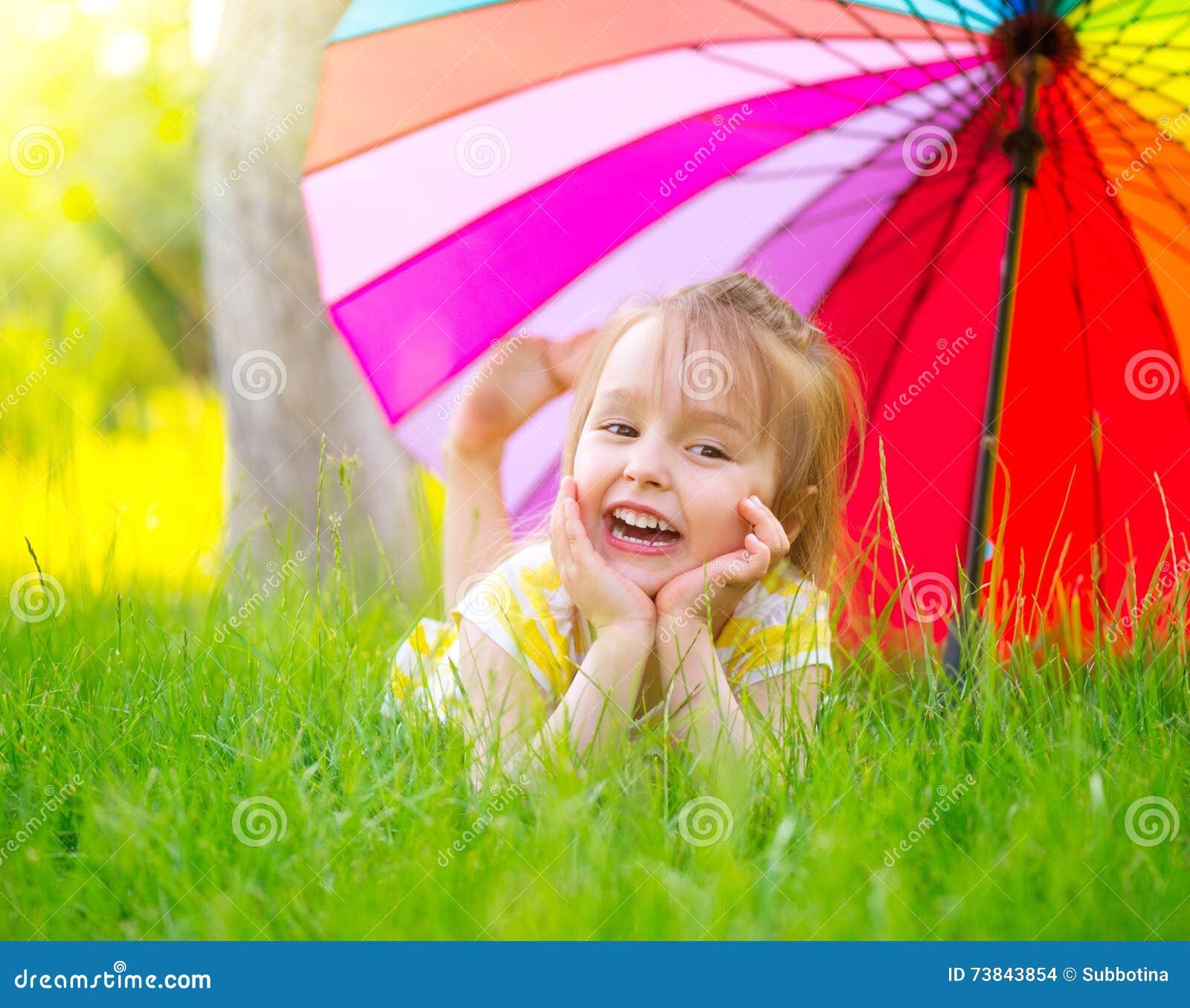 Μικρό κορίτσι που βρίσκεται στην πράσινη χλόη κάτω από τη ζωηρόχρωμη ομπρέλα