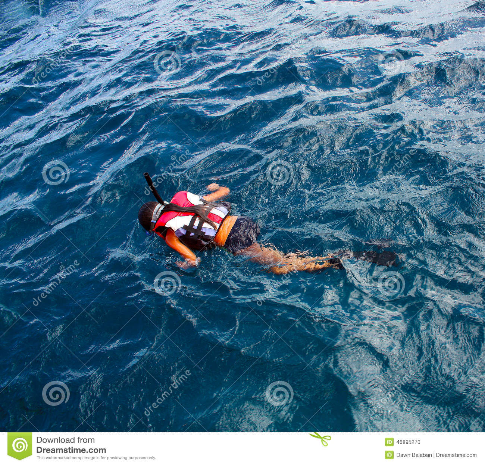 Μικρό κορίτσι που κολυμπά με αναπνευτήρα στον ωκεανό