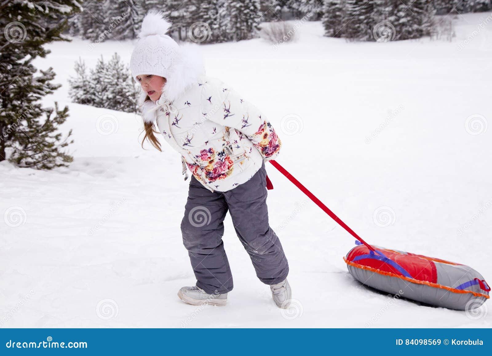Μικρό κορίτσι που τραβά τη σωλήνωση χιονιού λουριών