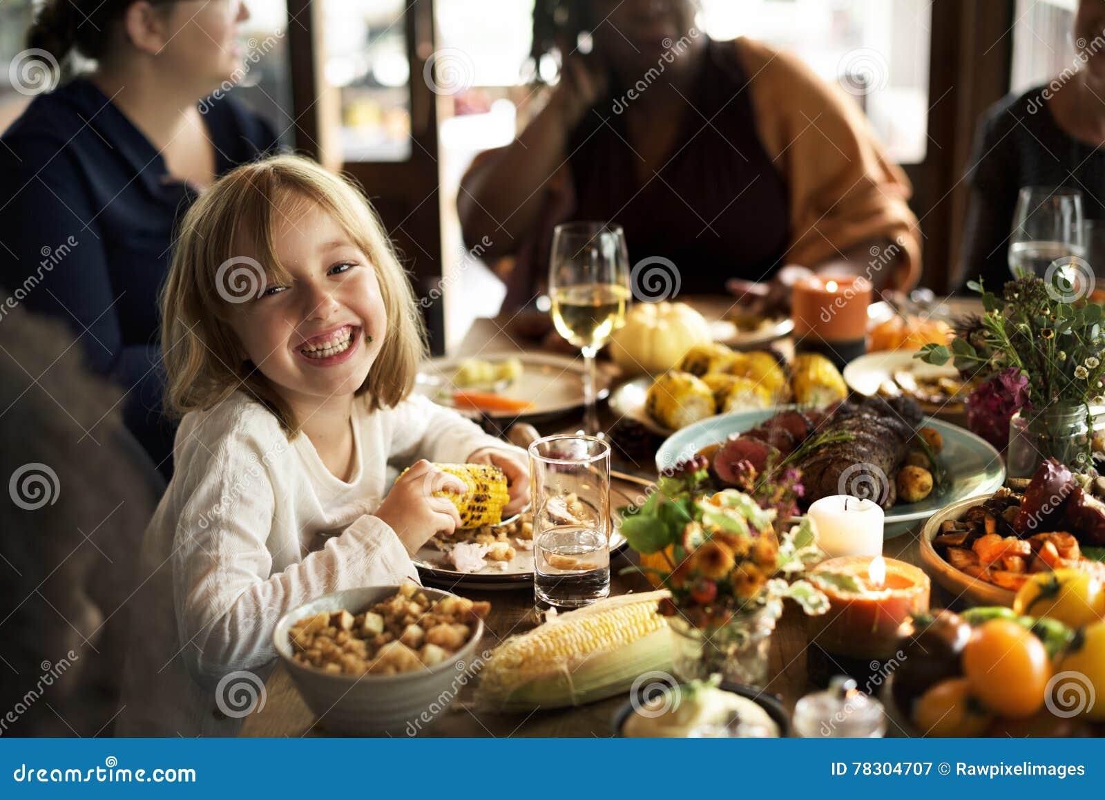 Μικρό κορίτσι που τρώει την έννοια εορτασμού ημέρας των ευχαριστιών καλαμποκιού