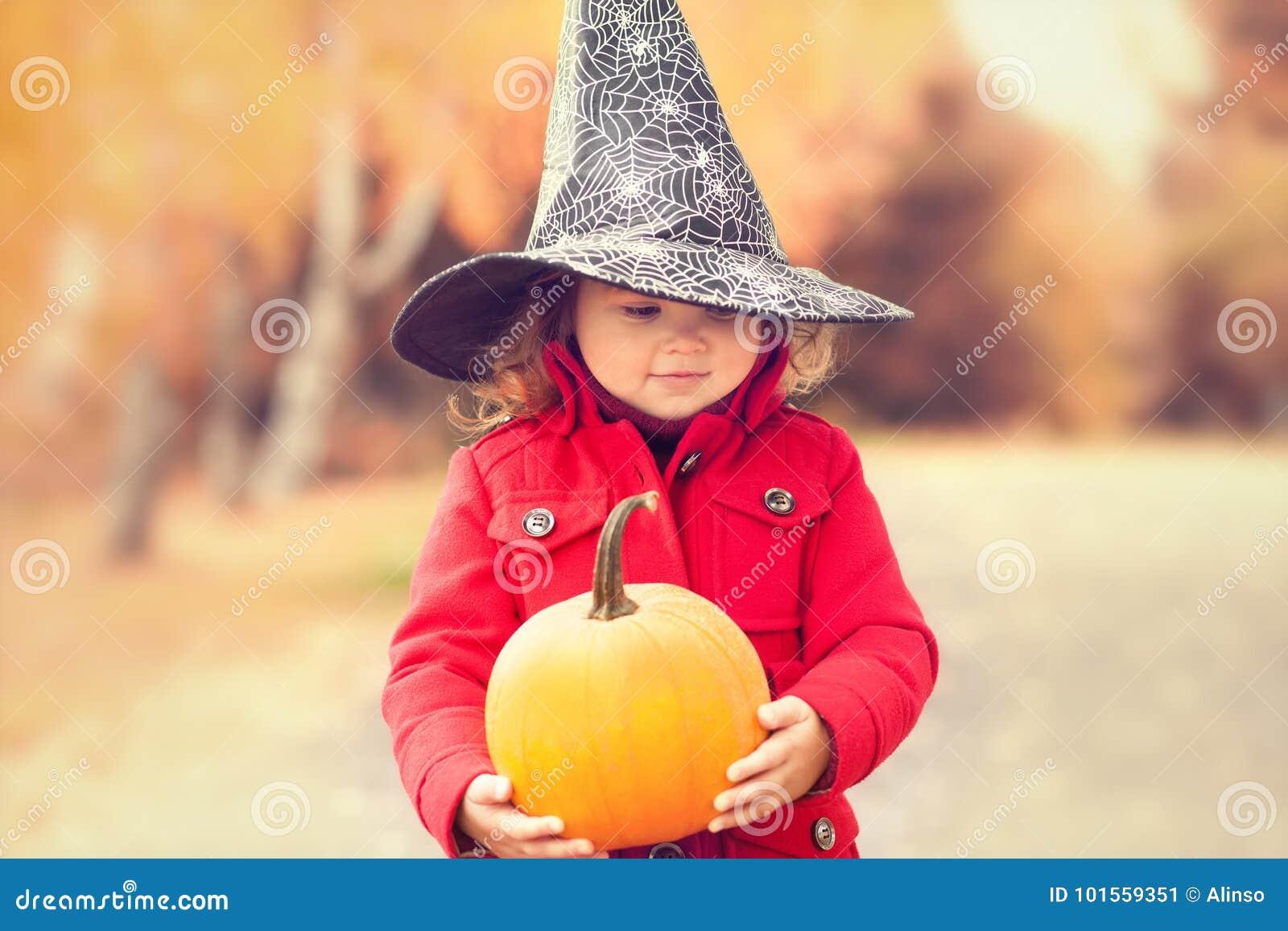 Μικρό κορίτσι που φορά το καπέλο μαγισσών αποκριών και το θερμό κόκκινο παλτό, που έχουν τη διασκέδαση στην ημέρα φθινοπώρου