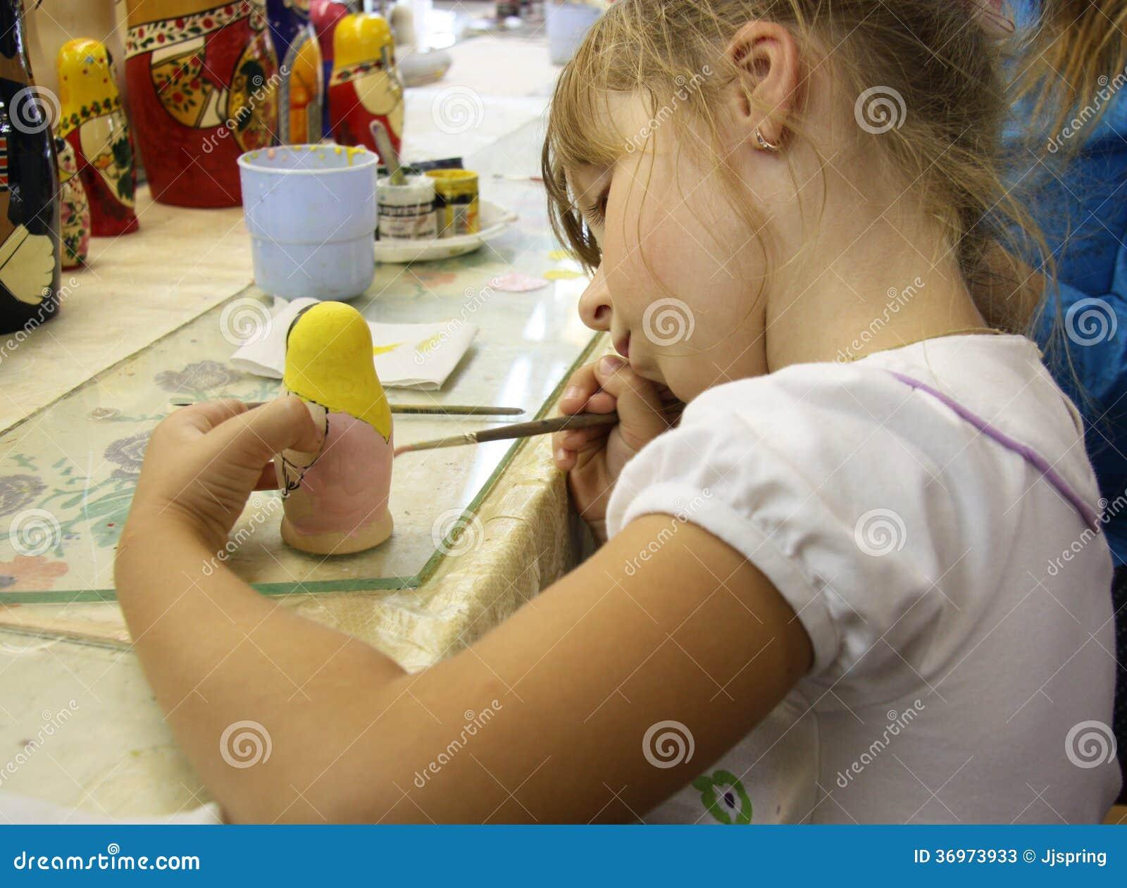 Μικρό κορίτσι που χρωματίζει μια ρωσική κούκλα matrioshka