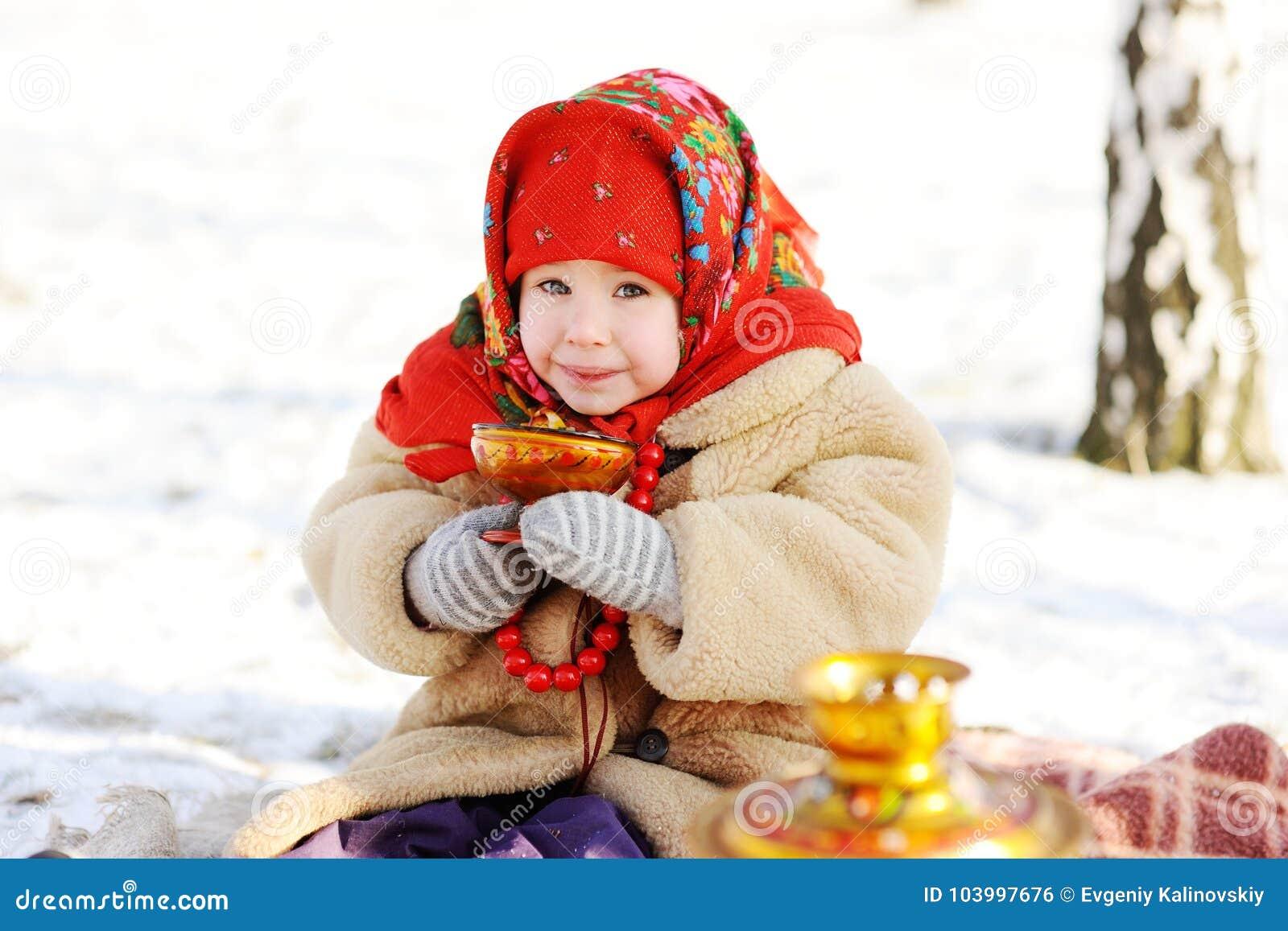 Μικρό κορίτσι σε ένα παλτό γουνών και ένα κόκκινο τσάι κατανάλωσης μαντίλι ρωσικό επάνω