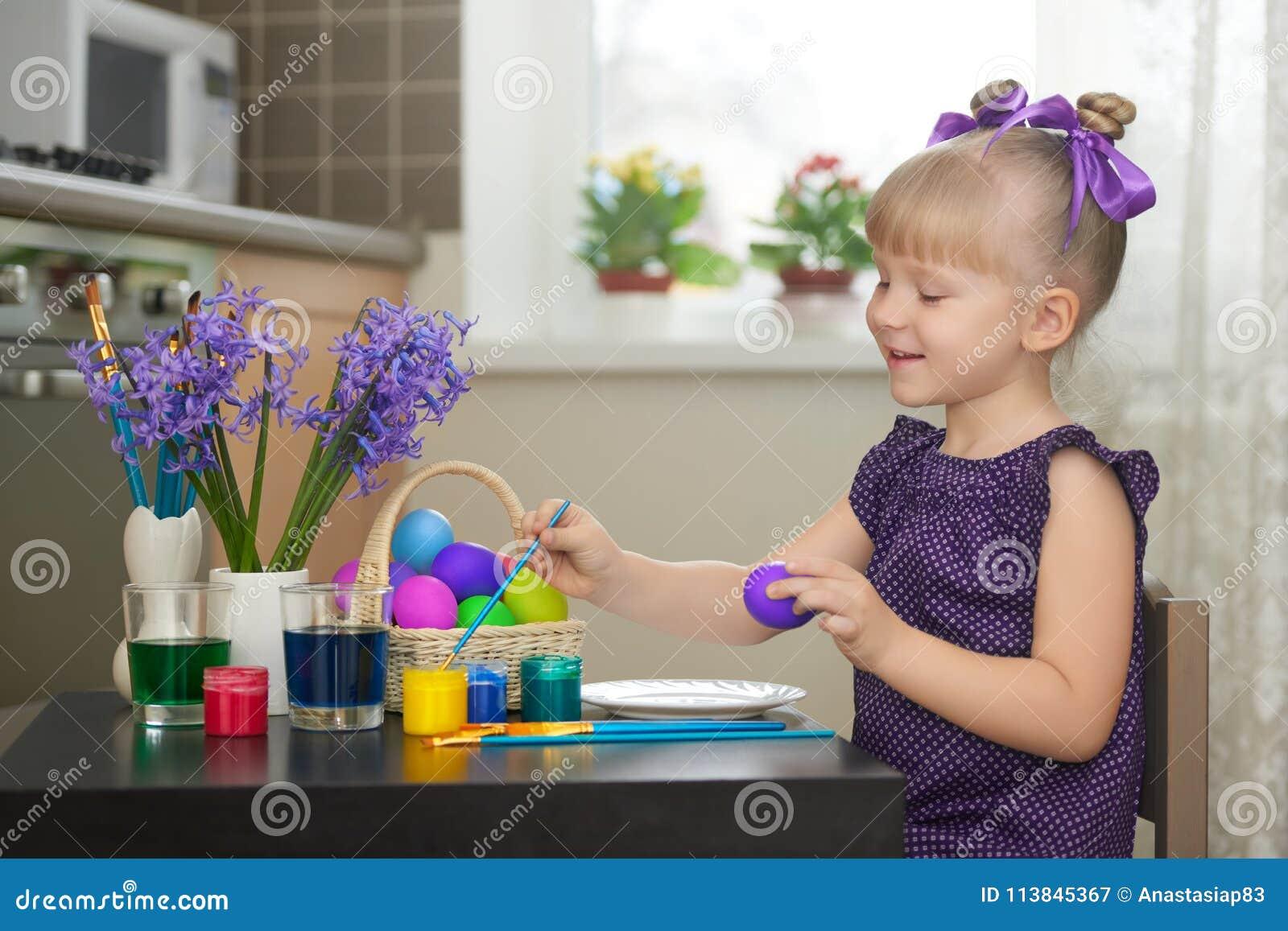 Μικρό κορίτσι στο ιώδες φόρεμα που διακοσμεί τα αυγά Πάσχας
