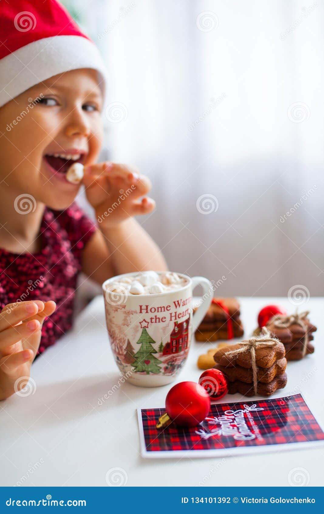 Μικρό κορίτσι στο καπέλο Santa που τρώει marshmallow από την κούπα με το κακάο και τα μπισκότα, εύθυμο Cristmas